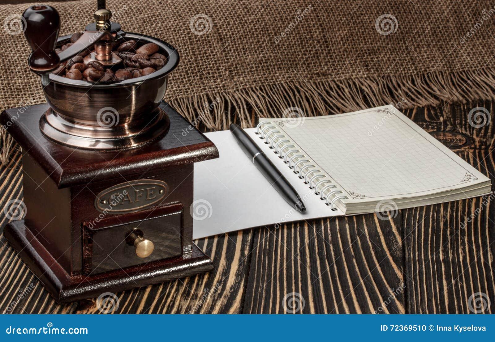磨咖啡器和笔记本在老木书桌上