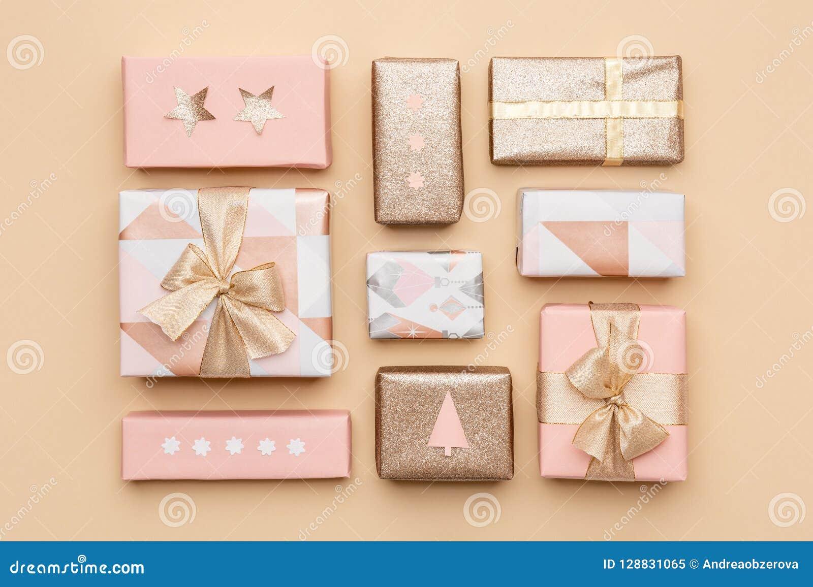 礼品包装材料构成 在金背景隔绝的美丽的北欧圣诞节礼物 桃红色和金子色的被包裹的礼物盒