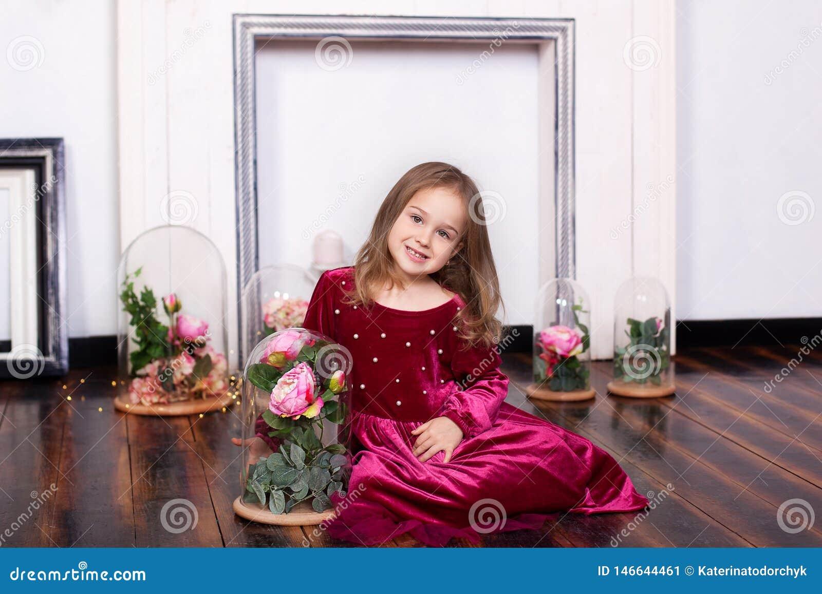 礼服的一逗人喜爱的女孩坐与一朵玫瑰的地板在烧瓶 r ?? 甜公主 Th