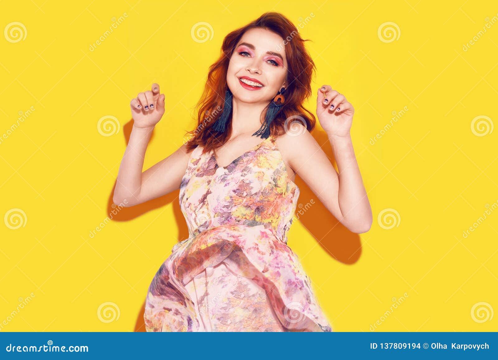 礼服的时尚女孩在黄色背景跳舞 有长期cerly飞行的头发的俏丽的女孩和桃红色组成 有美国钞票的女孩