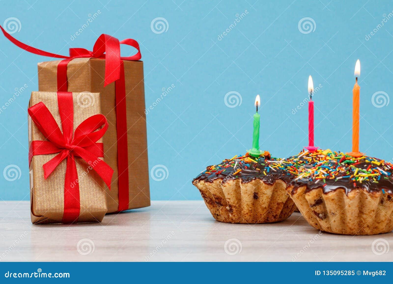礼物盒和生日杯形蛋糕与烧欢乐蜡烛在蓝色背景