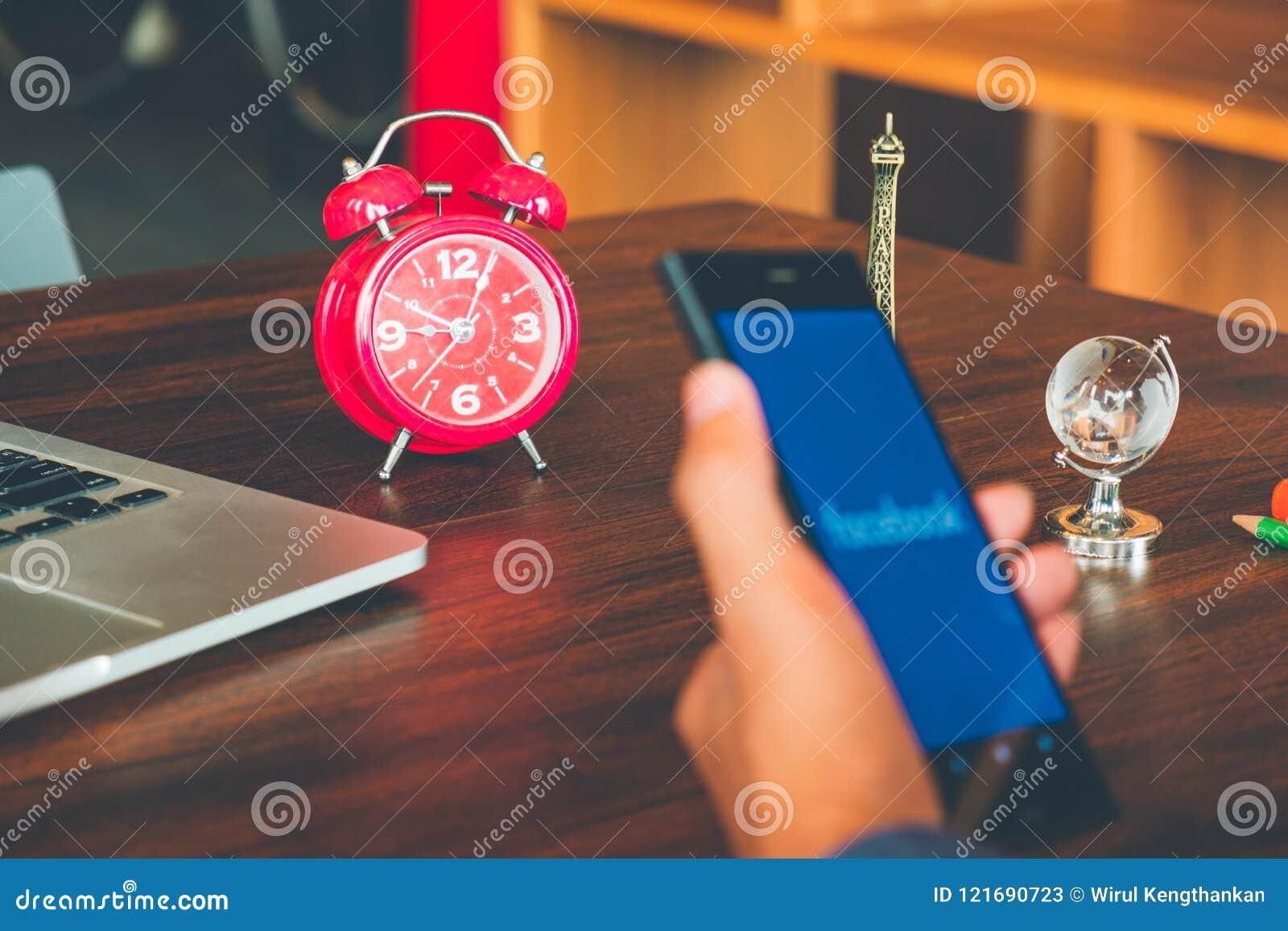 社会媒介时间安排概念、闹钟和手举行