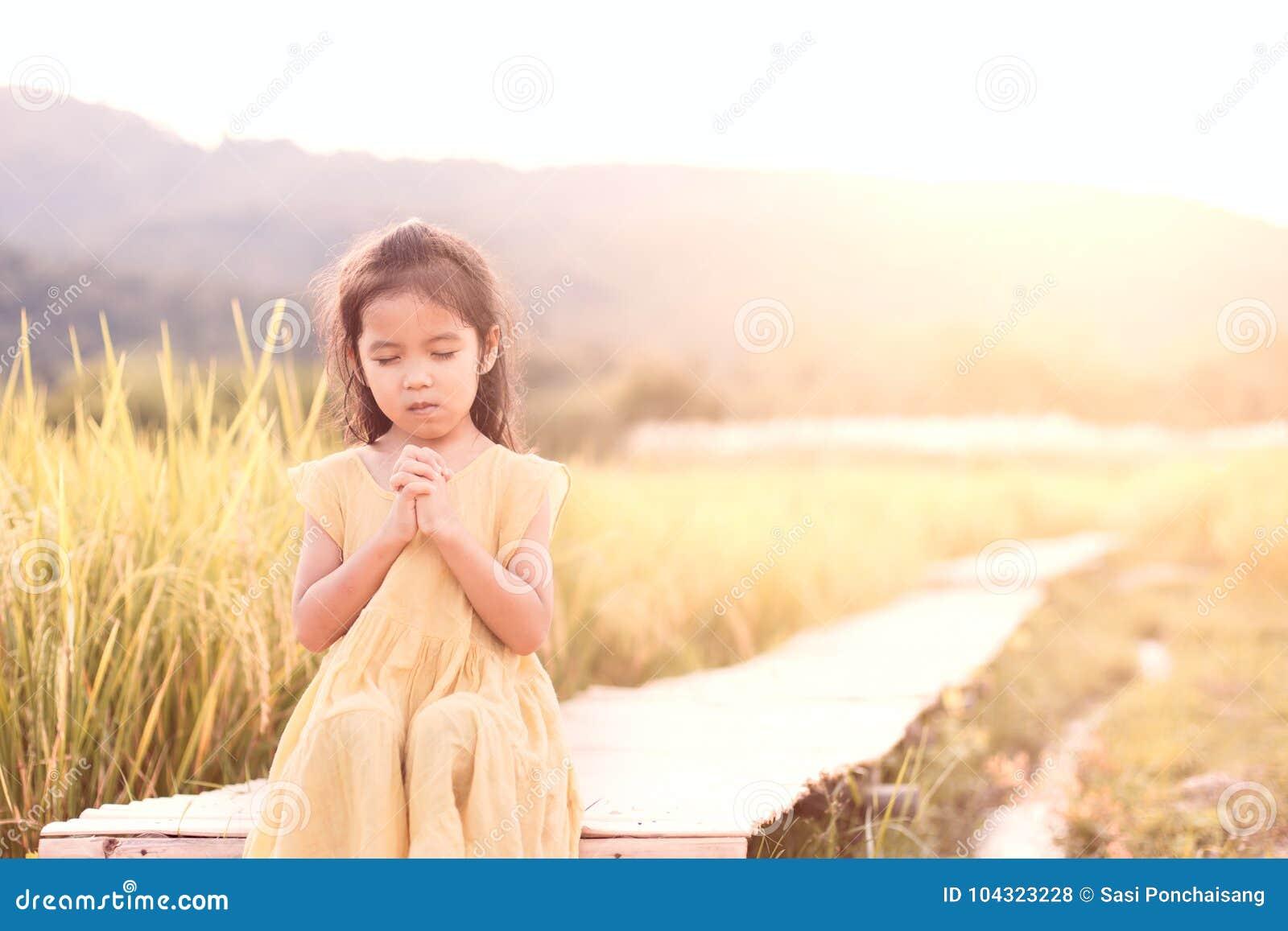 祈祷与折叠的逗人喜爱的亚裔小孩女孩她的手