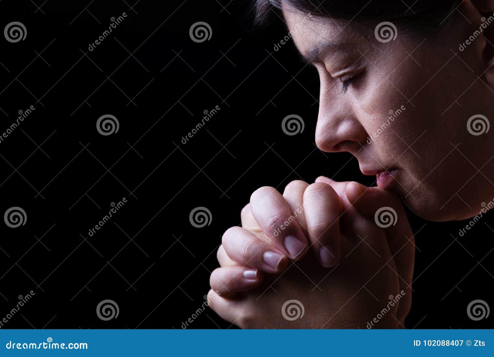 祈祷忠实的妇女,手在崇拜折叠了给神