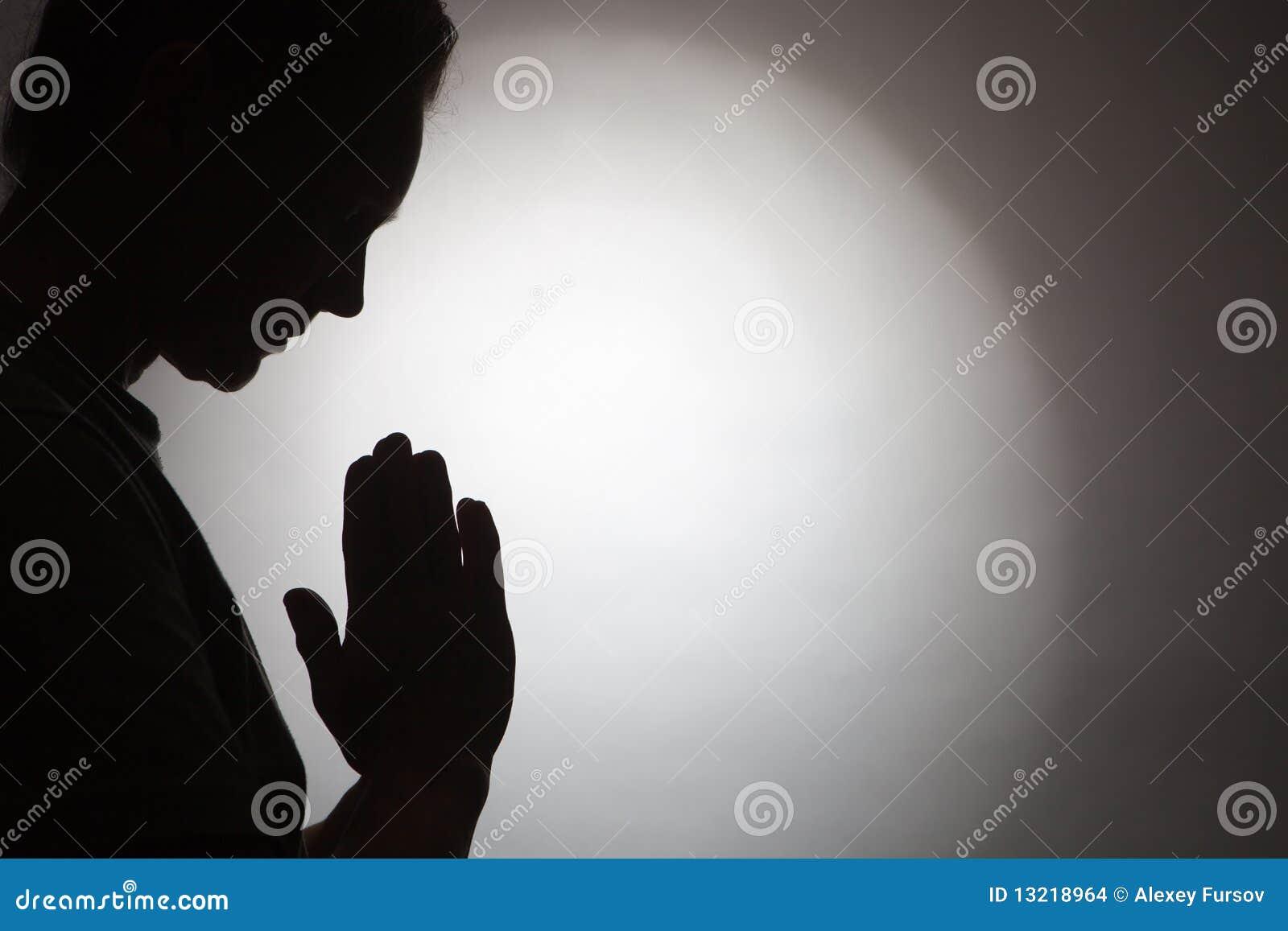 黑人祈祷的剪影妇女.