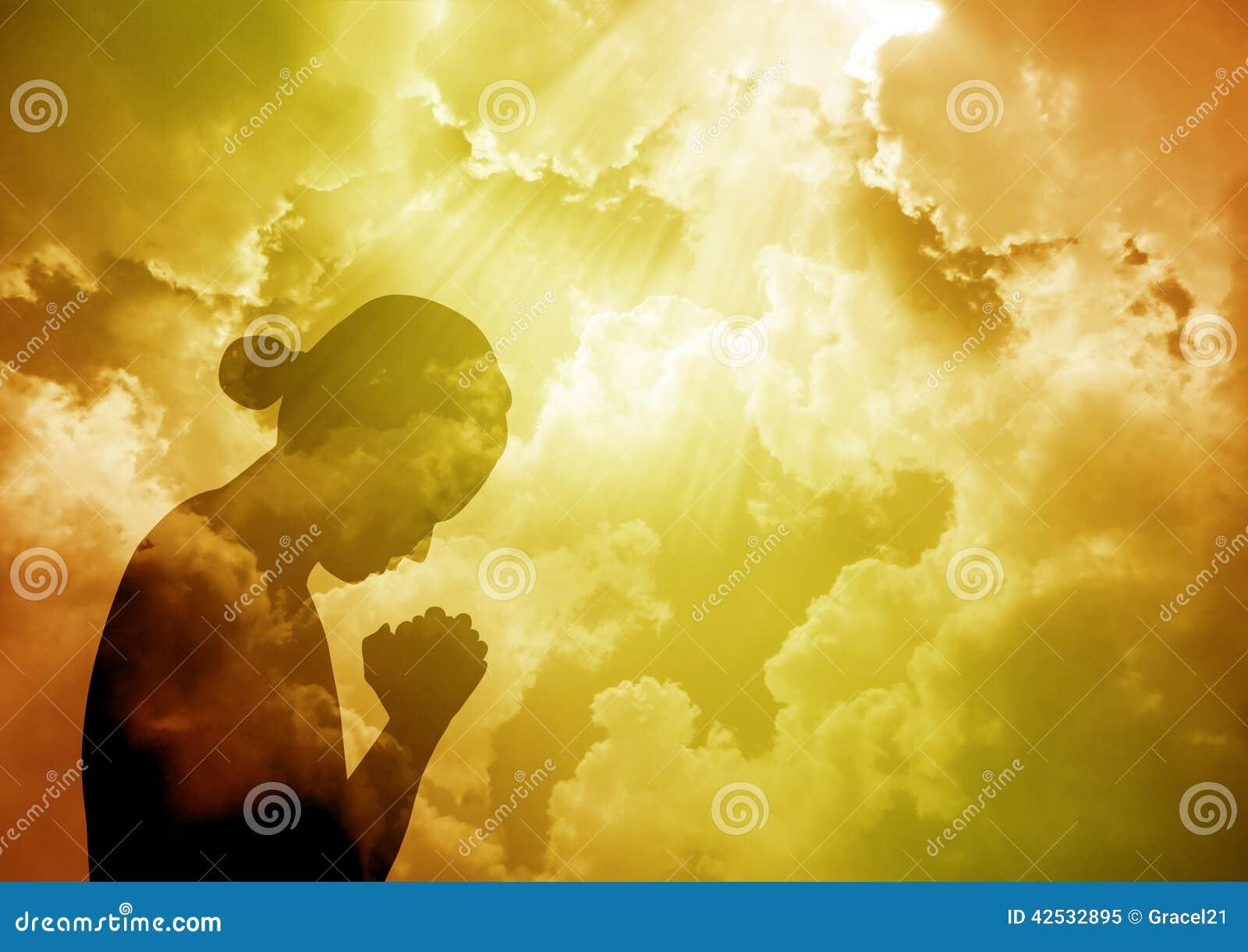 祈祷在日落的少妇剪影.