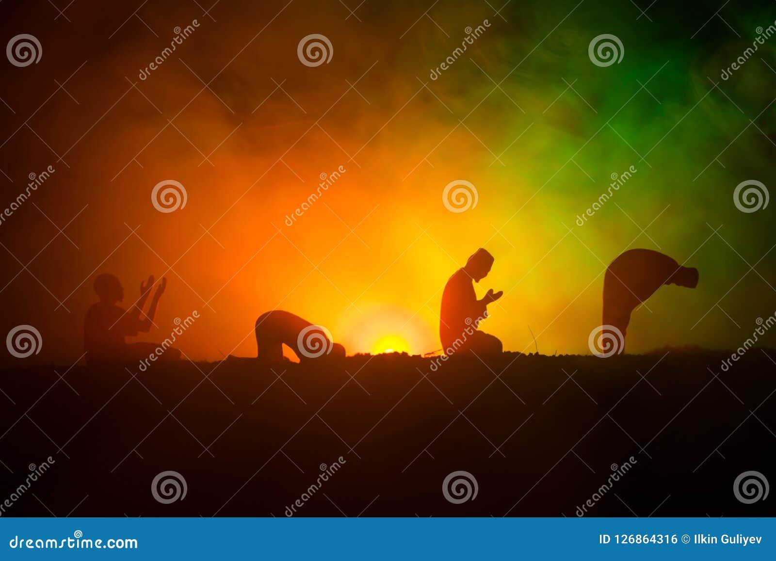 祈祷被定调子的有雾的背景的回教人剪影  赖买丹月Kareem背景 穆斯林Eid假日装饰 祈祷的peop
