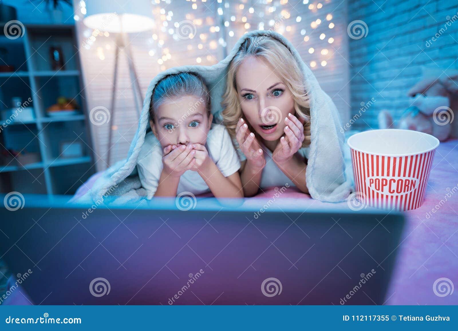 祖母和孙女在晚上在家观看在膝上型计算机的电影