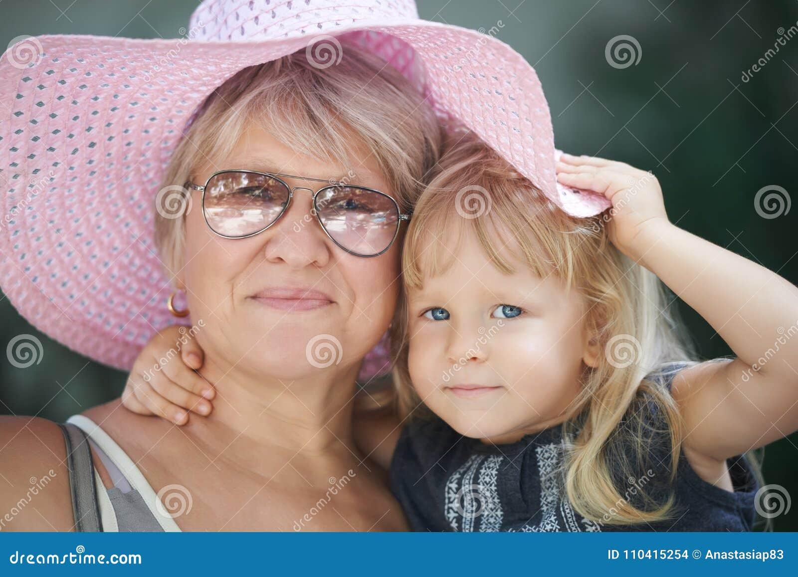 祖母的街道画象有孙女的一个桃红色夏天帽子的