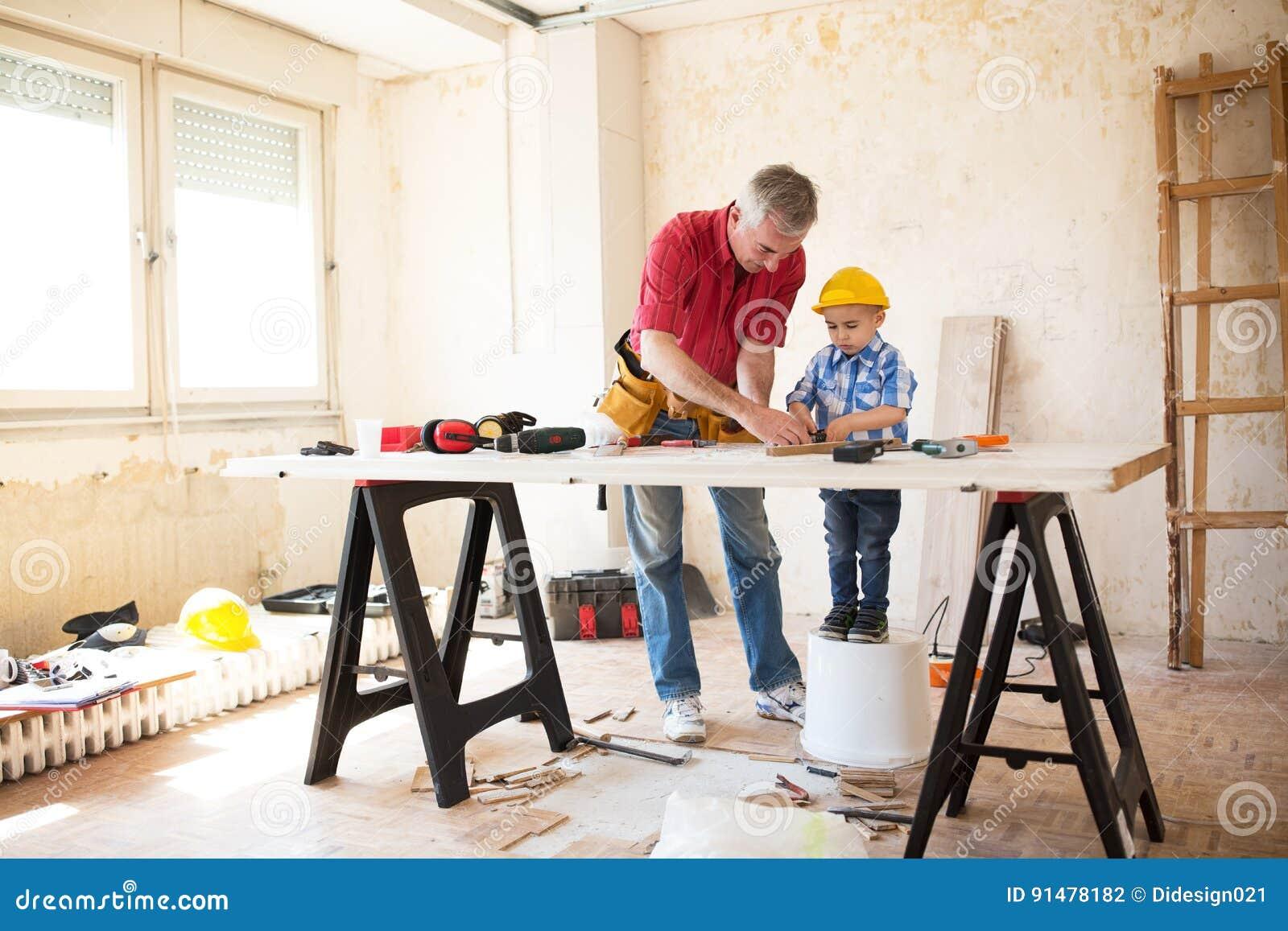 祖父和孙子与木头一起使用
