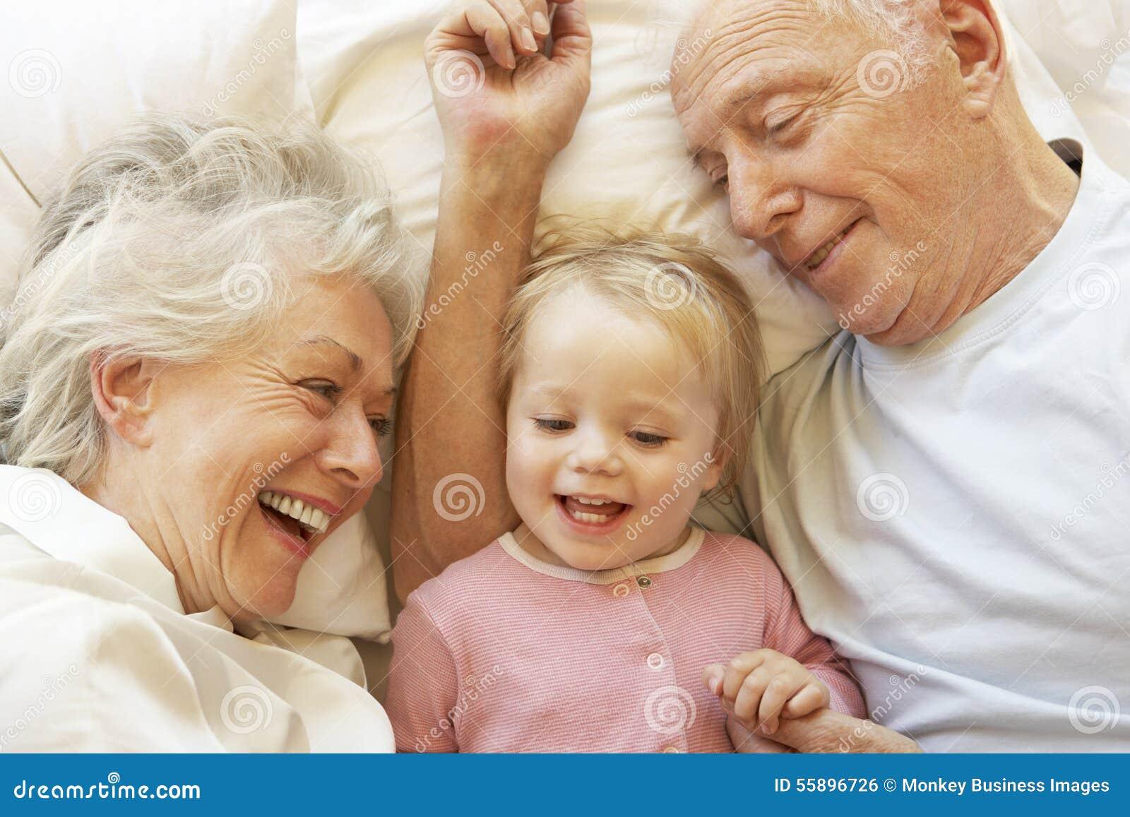 祖父母在床上的拥抱孙女