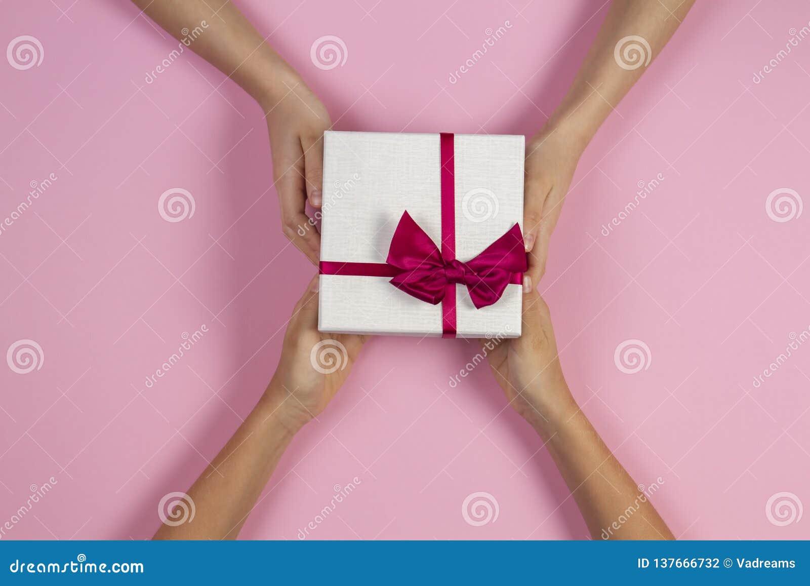 祝贺背景 给和接受有丝带的两只人手顶视图一个当前礼物盒在桃红色
