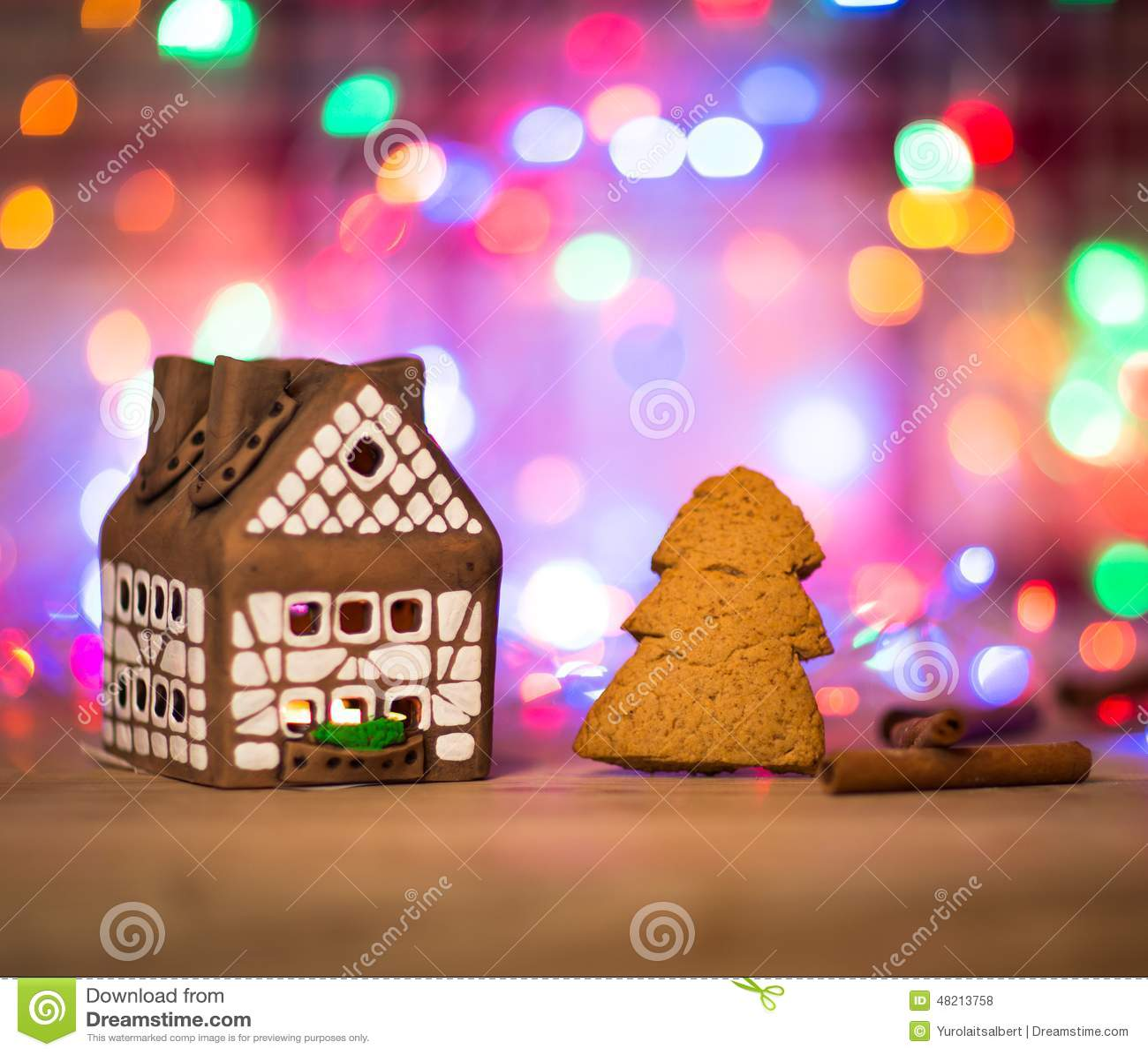 与蜡烛光,狭窄的景深和里面背景光的神仙的圣诞节房子蛋糕.图片