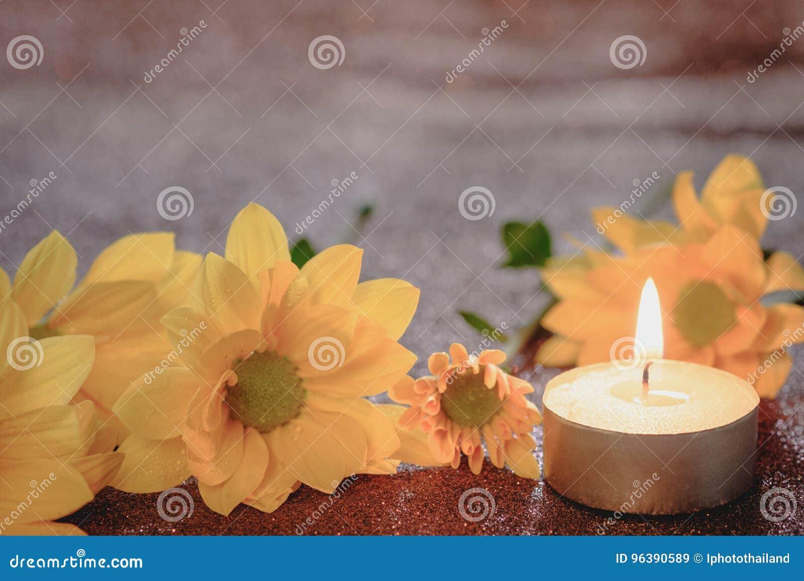 祷告和希望概念 减速火箭的蜡烛光和黄色花与光线影响和闪烁抽象背景与bokeh defo
