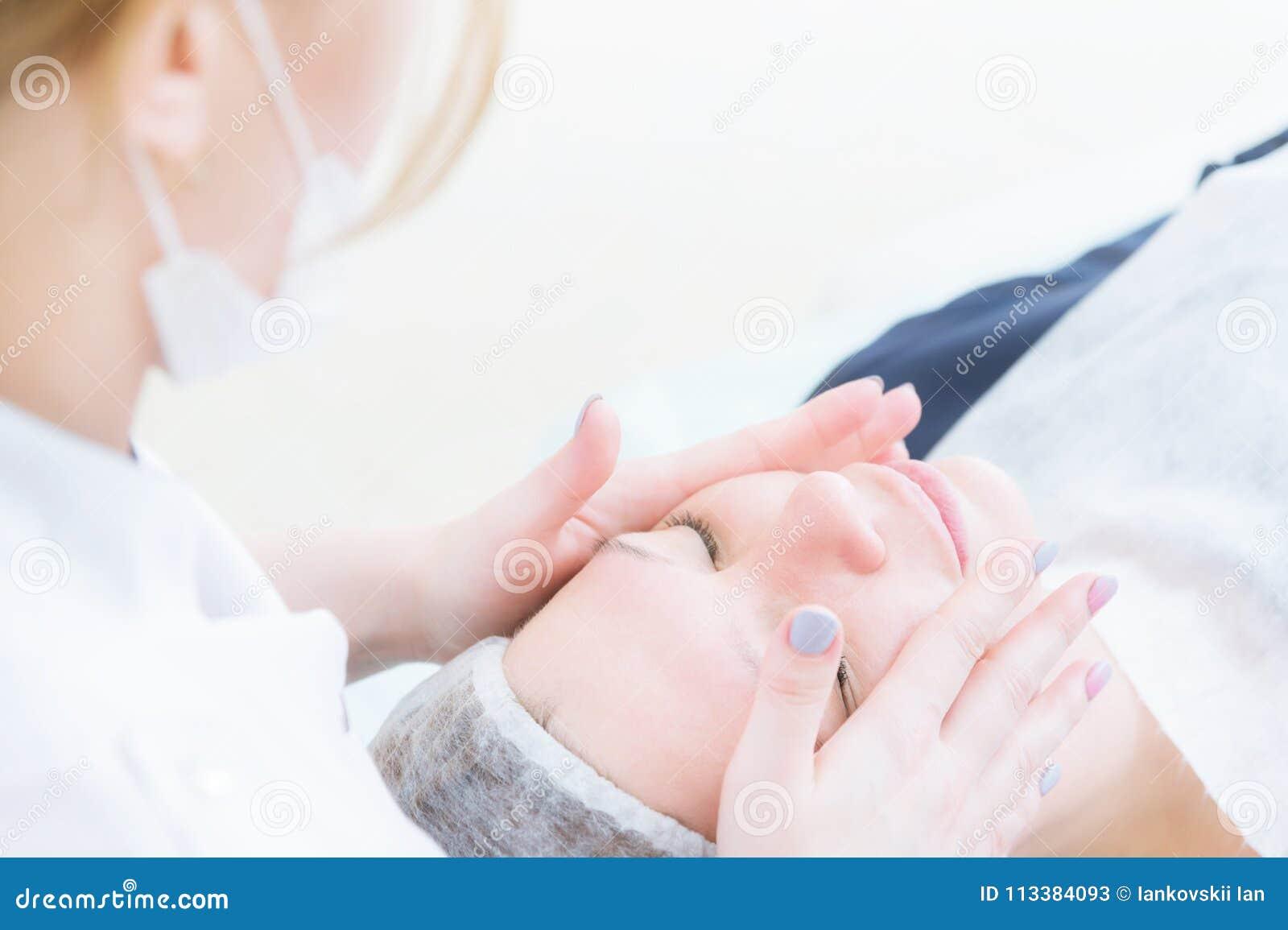 秀丽交谊厅 一名医疗美容师的特写镜头桃红色手套的做面孔按摩一名美丽的妇女 整容术
