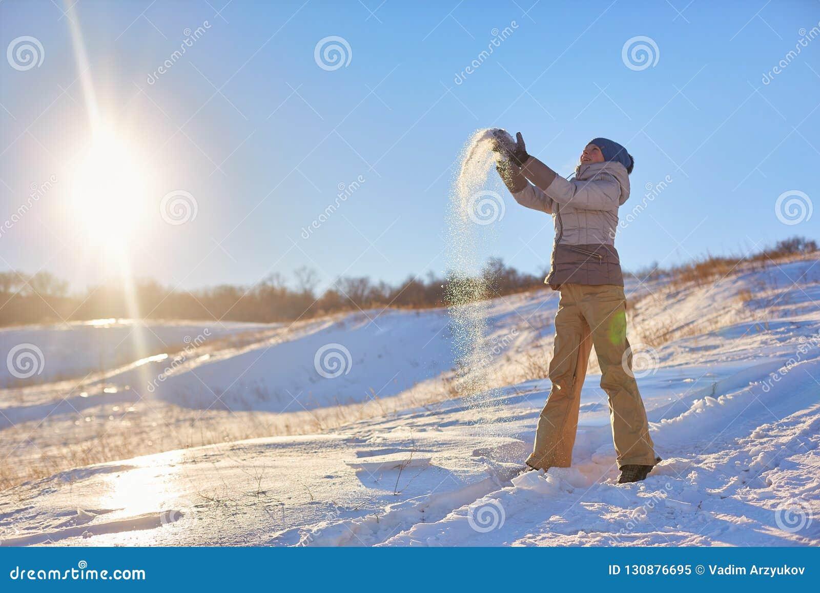 秀丽冬天女孩吹的雪在冷淡的冬天公园 户外 飞行雪花 晴朗的日 由后照 秀丽年轻人