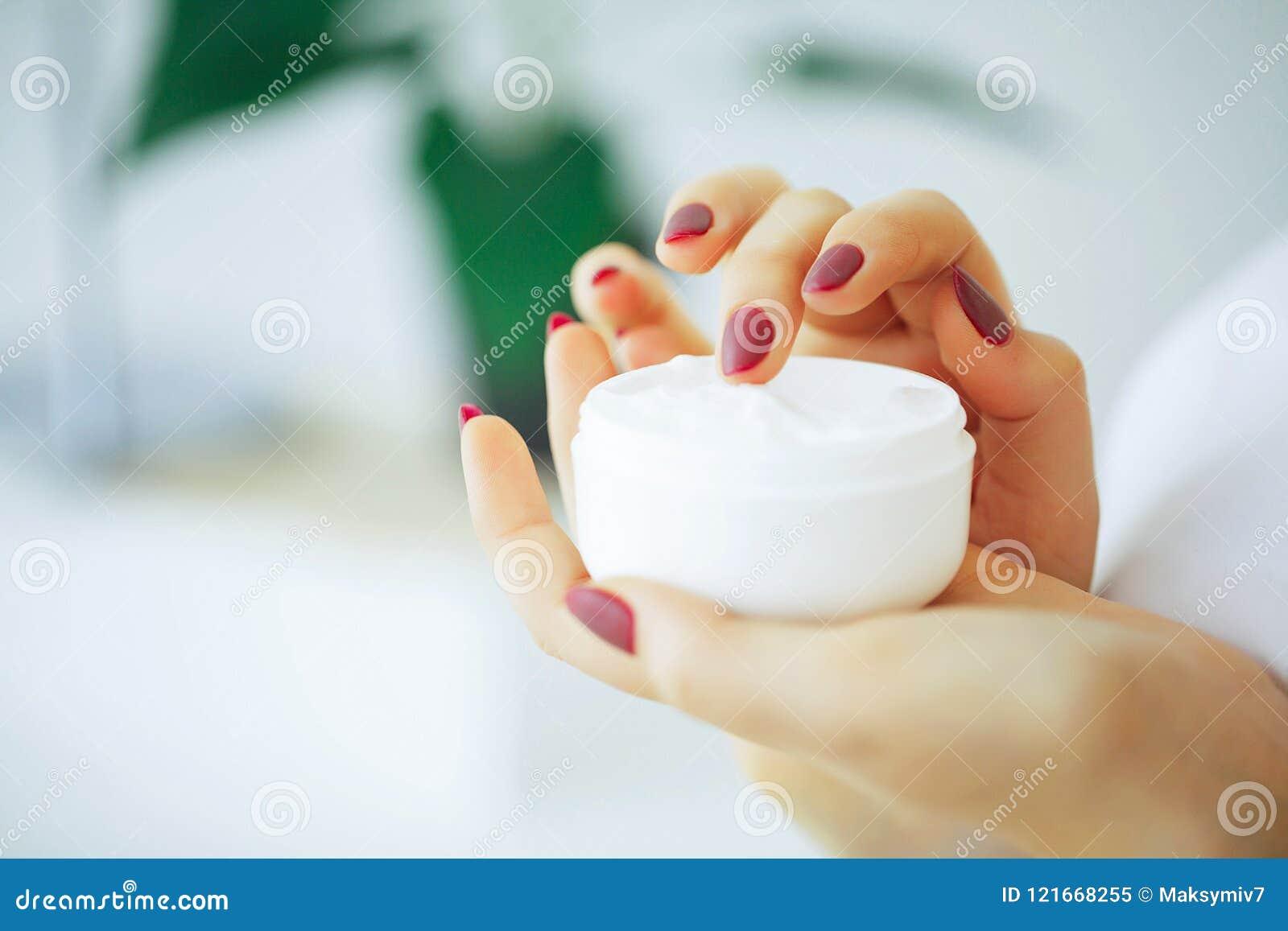 秀丽和关心 拿着面霜的女孩 有纯净的皮肤的一名妇女