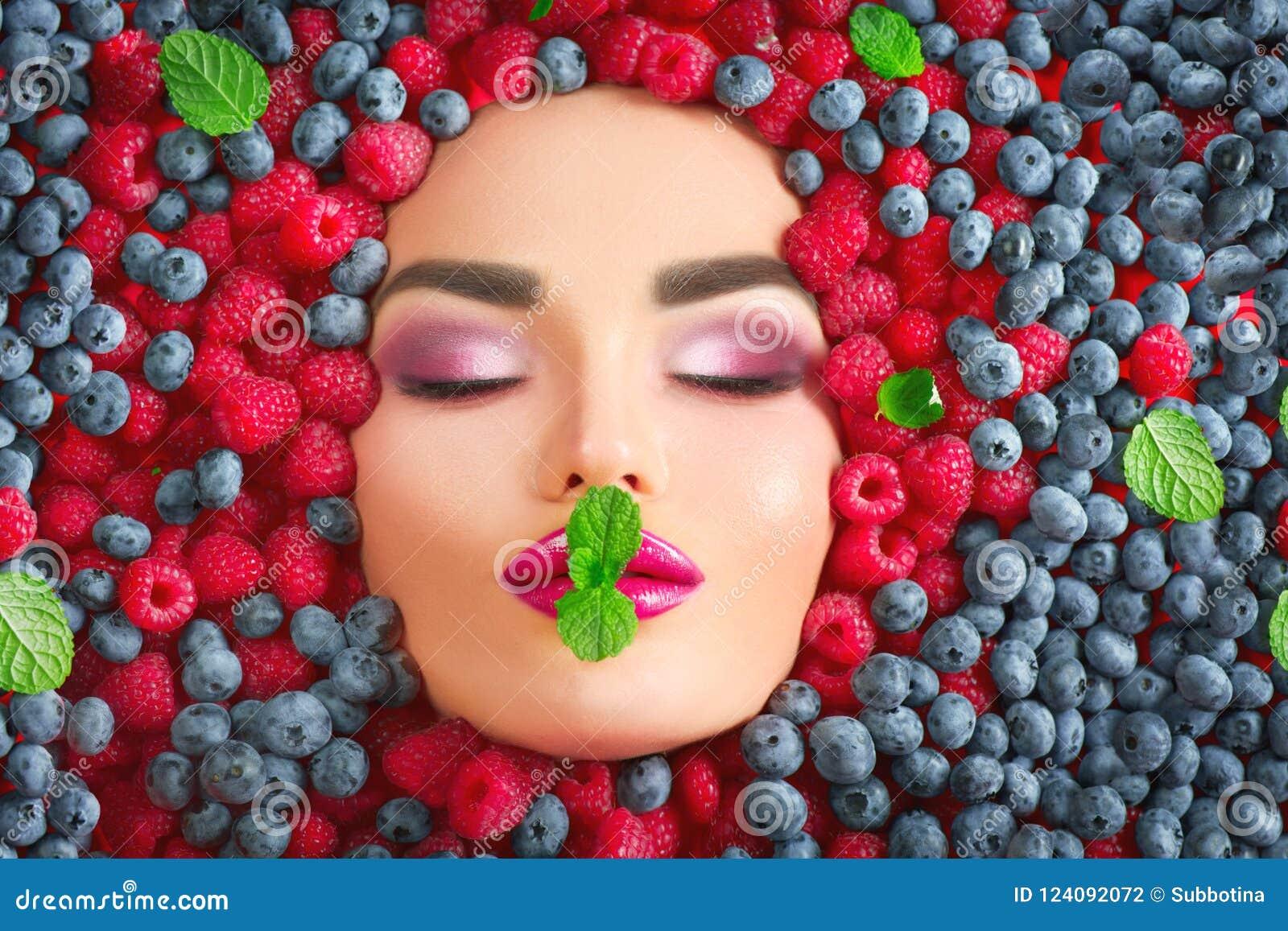 秀丽在新鲜的成熟莓果的时装模特儿女孩 面对在五颜六色的莓果特写镜头 美丽的构成,水多和性感的嘴唇