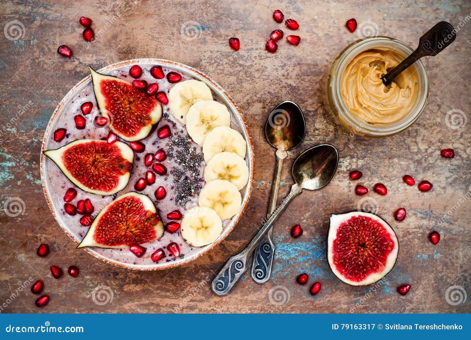 秋天和冬天早餐集合 Acai superfoods圆滑的人滚保龄球与chia种子,石榴,香蕉,新鲜的无花果,榛子黄油