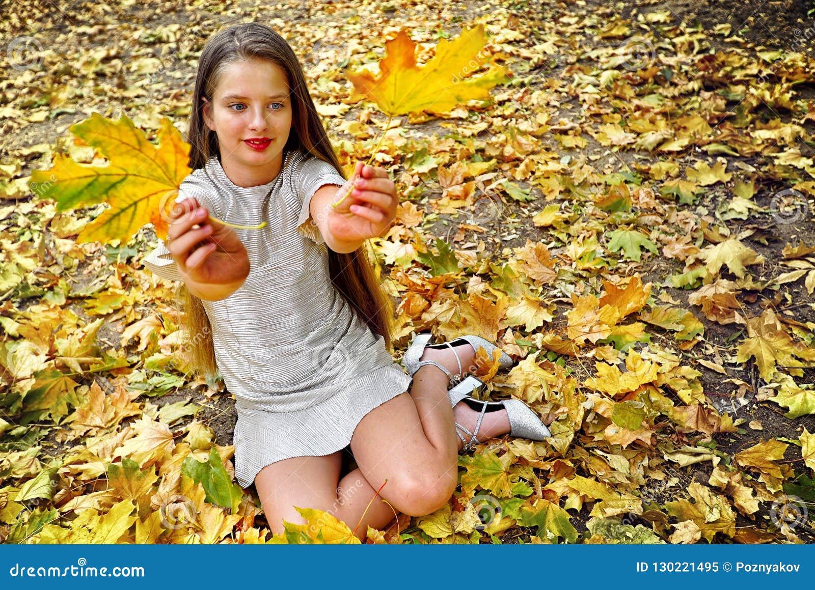 秋天时尚礼服儿童女孩坐的秋天离开公园室外