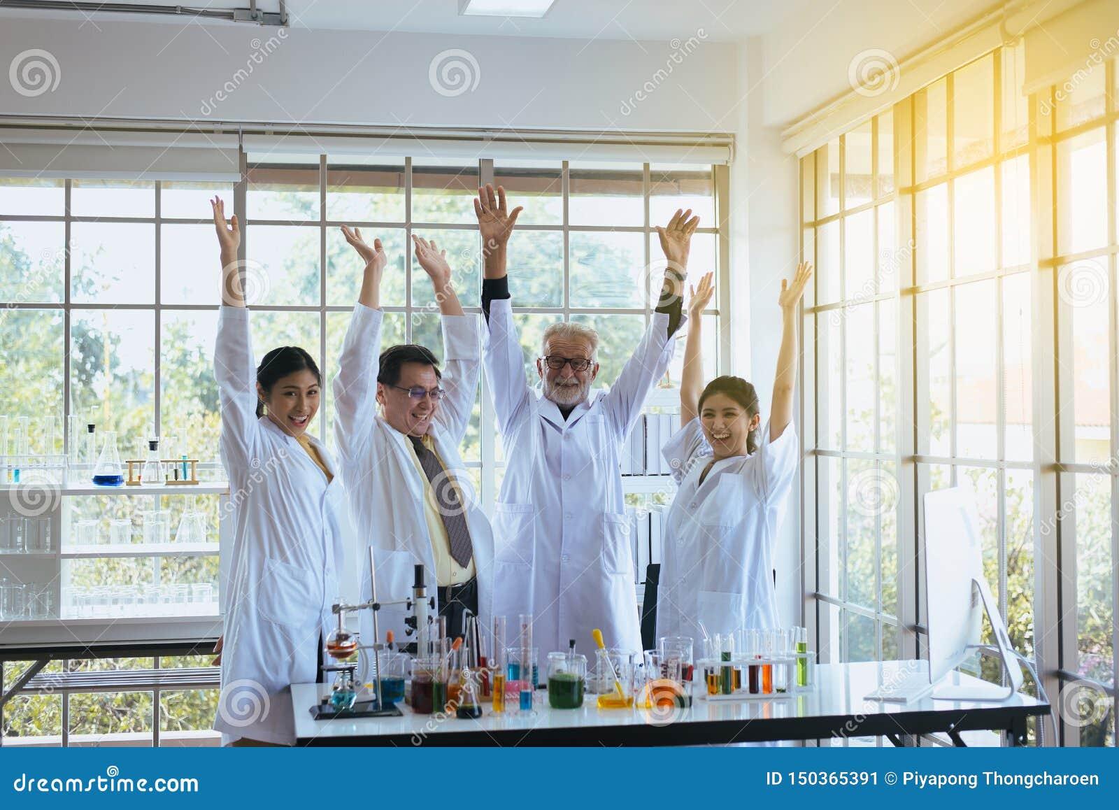科学家一起手rais,小组变化在实验室,成功和reserch工作的人配合
