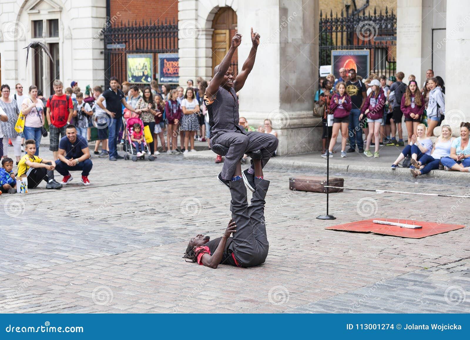 科文特花园市场、普遍的购物和旅游胜地,黑人马戏团演员展示在街道,伦敦,英国上的