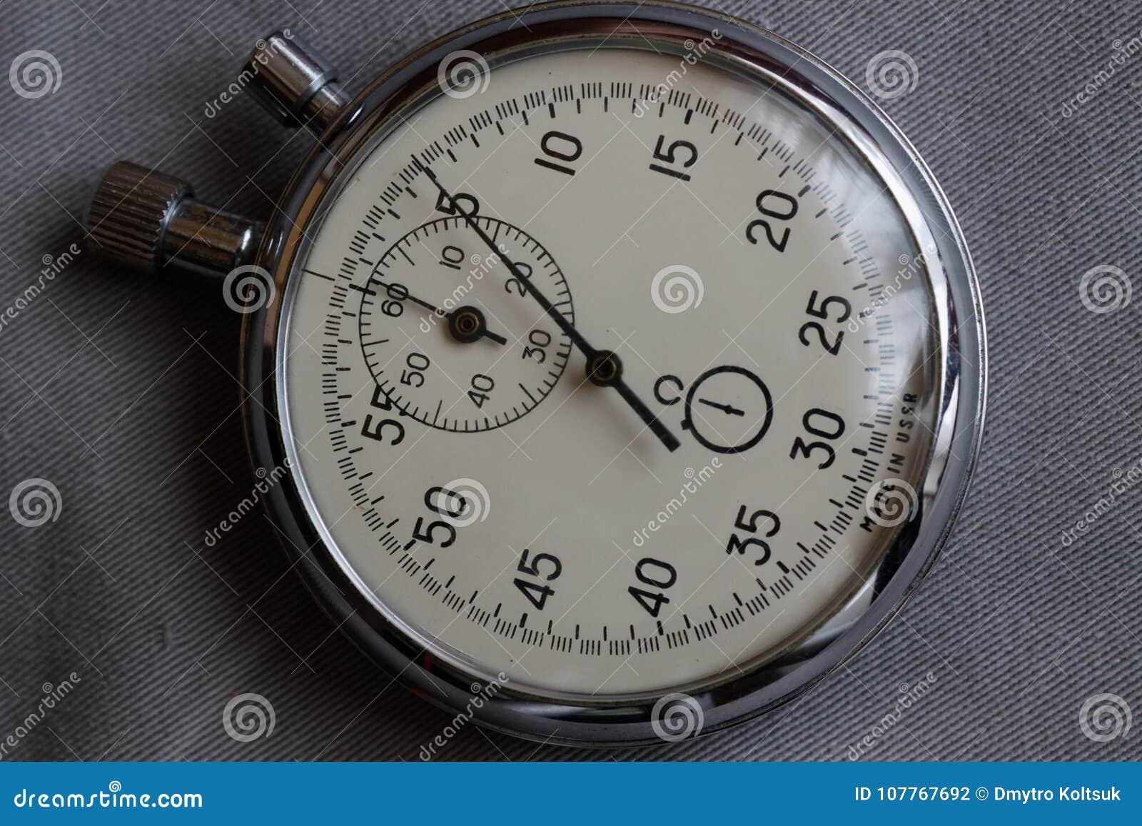 秒表,在白色牛仔布背景、价值措施时间、老时钟箭头分钟和第二个准确性定时器纪录