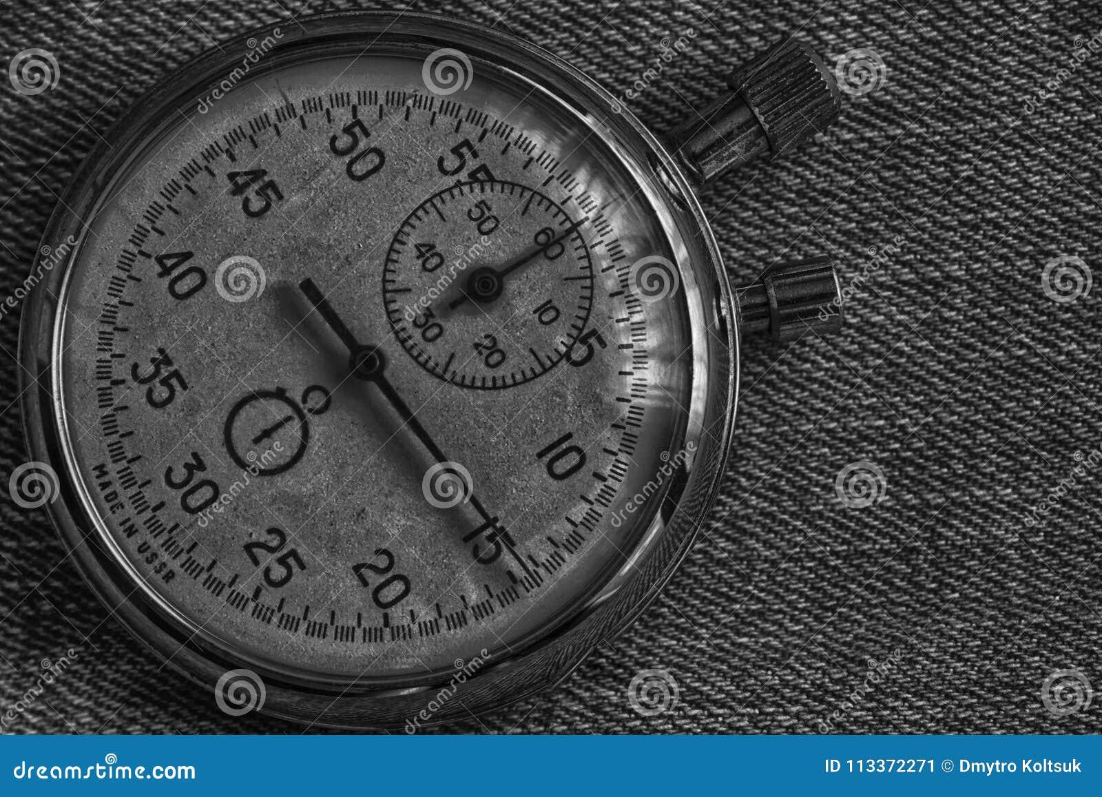 秒表,在破旧的牛仔布背景、价值措施时间、老时钟箭头分钟和第二个准确性定时器纪录
