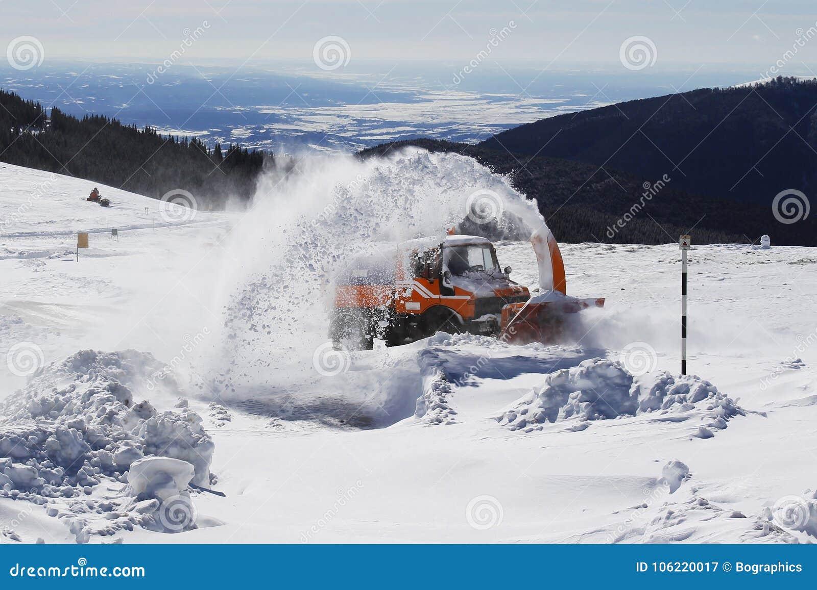 积雪的清除在山路的机器吹风机