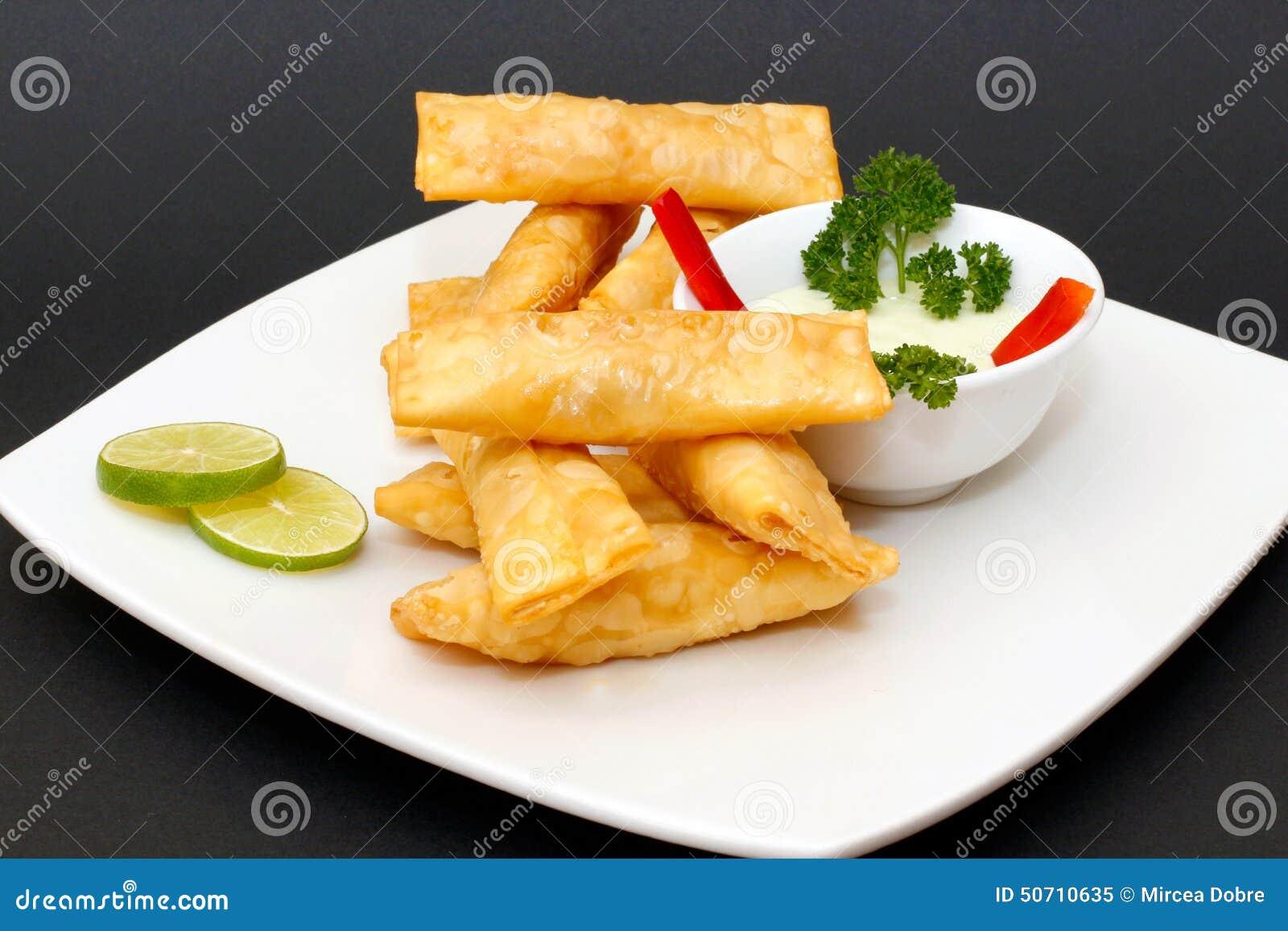称Tequenos的拉丁美洲的开胃菜由油煎的馄饨制成充满乳酪和供食与鳄梨调味酱捣碎的鳄梨酱