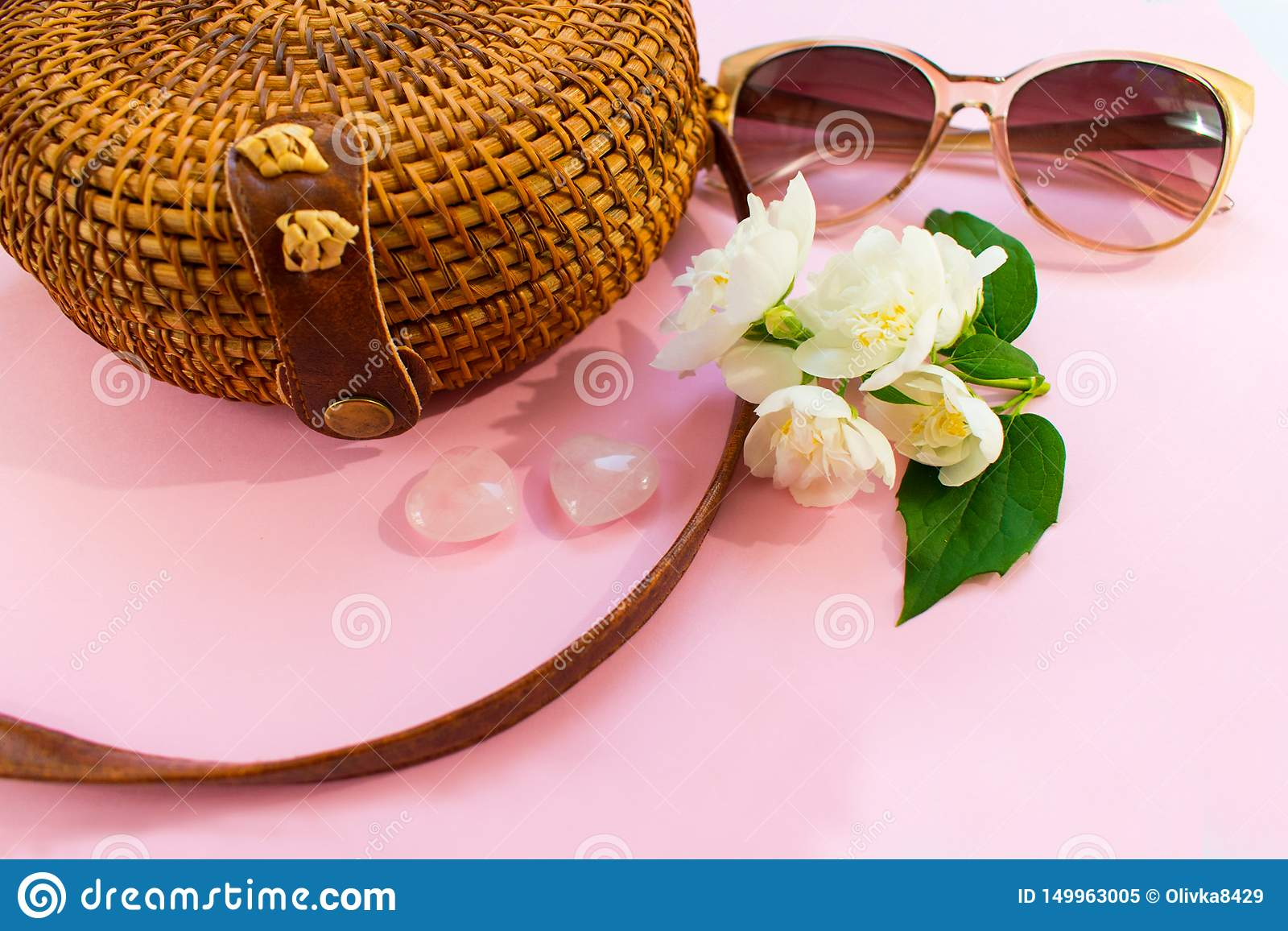 秸杆时髦的现代妇女的袋子和太阳镜和白色茉莉花花在桃红色背景 E