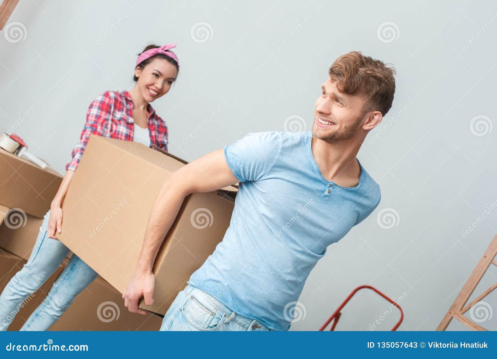 移动向新的地方运载的箱子的年轻夫妇一起谈微笑dreamful