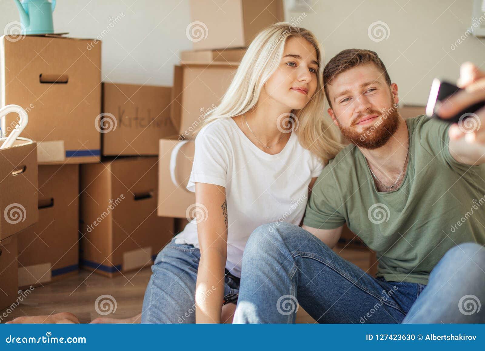 移动新的家的夫妇 坐地板和放松在打开以后 做与智能手机的selfie
