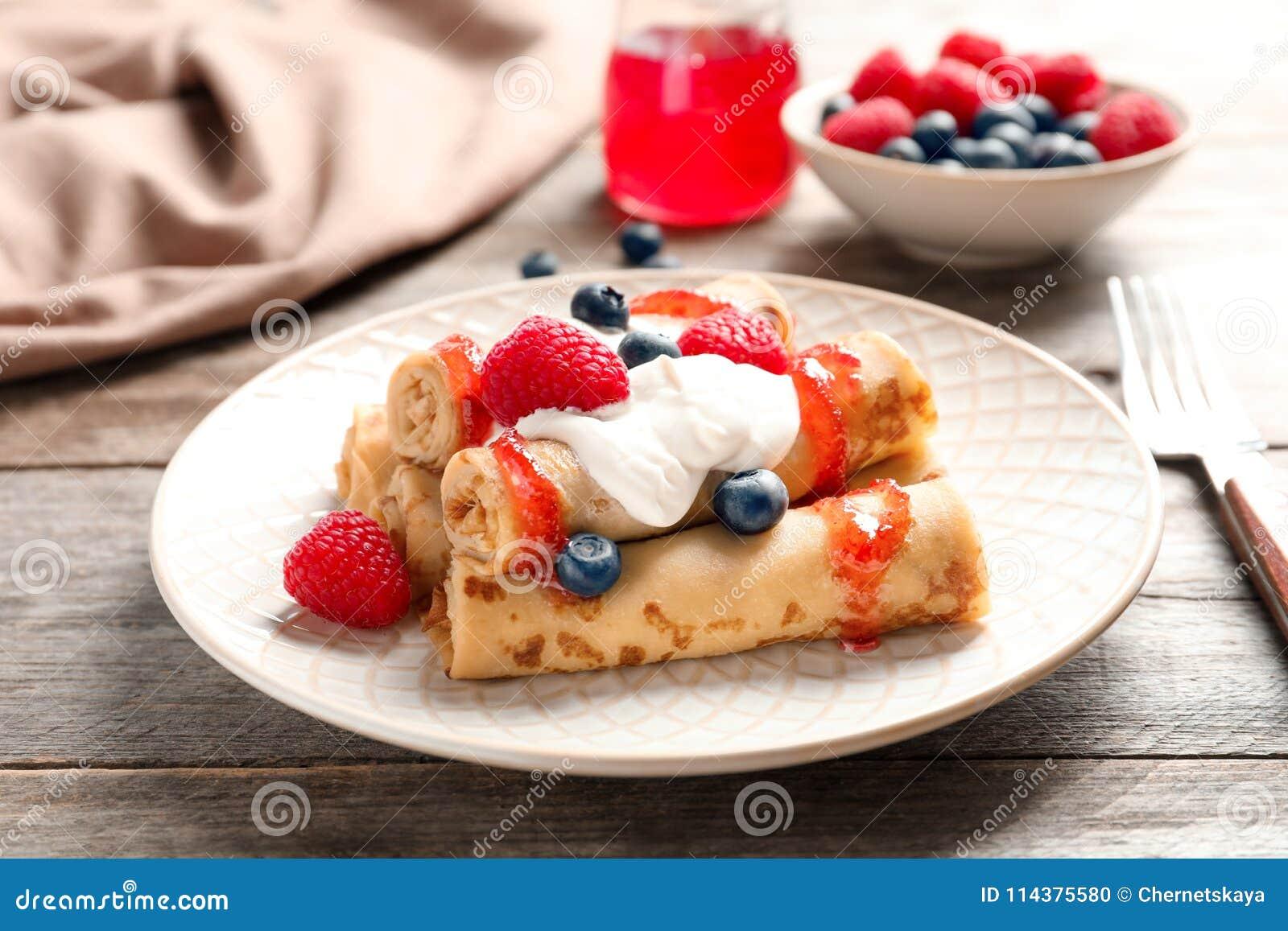 稀薄的薄煎饼服务用糖浆、奶油和莓果