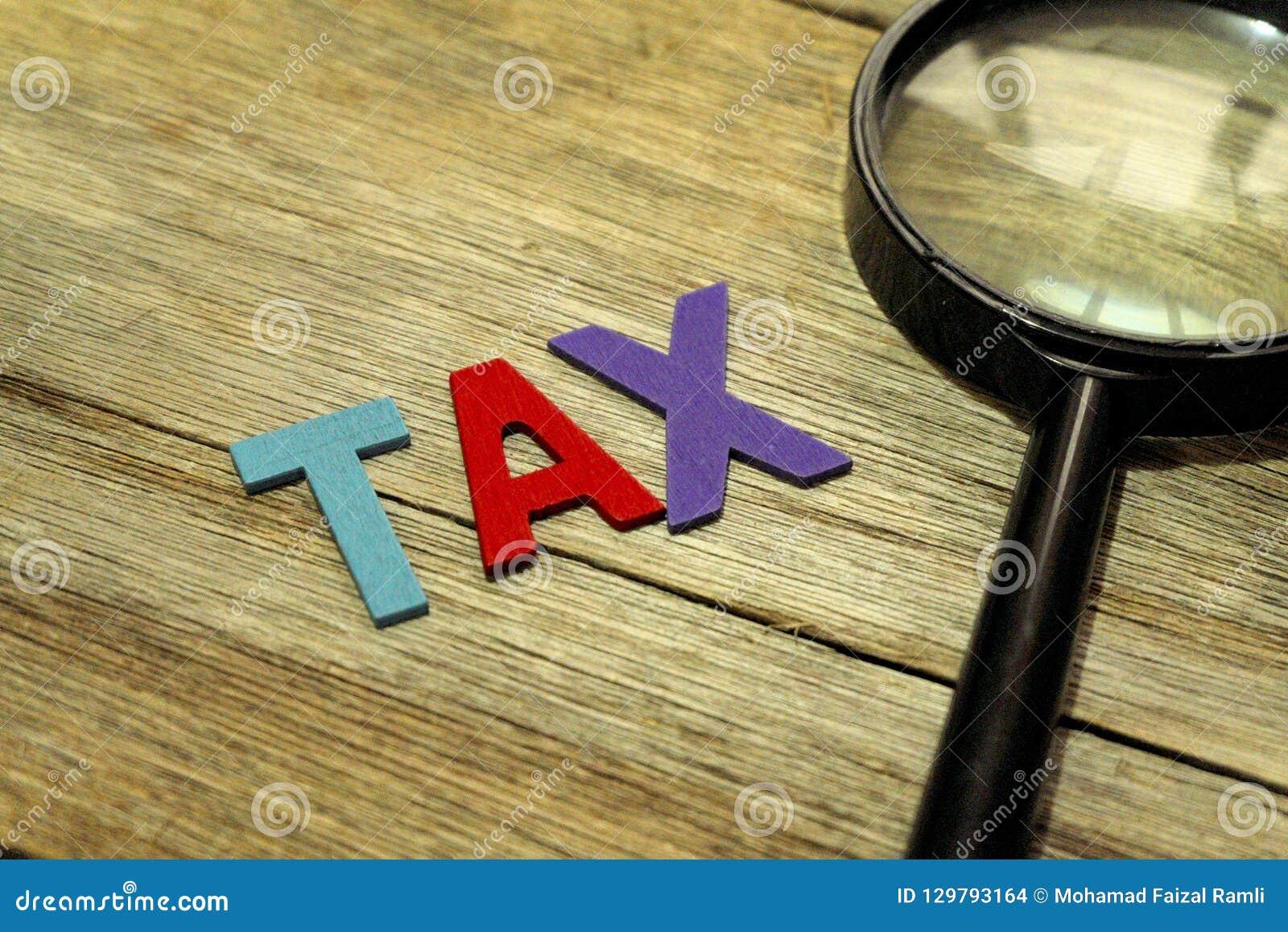 税概念放大器和五颜六色的木字母表在木背景