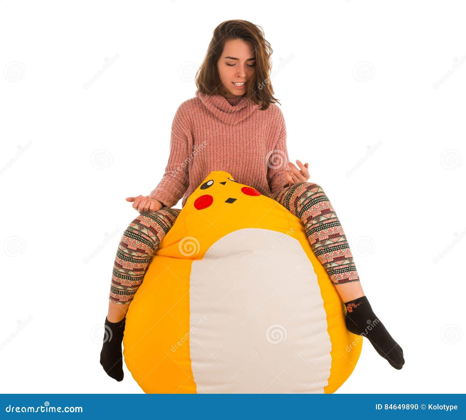 滑稽的妇女坐在白色ba隔绝的黄色装豆子小布袋椅子