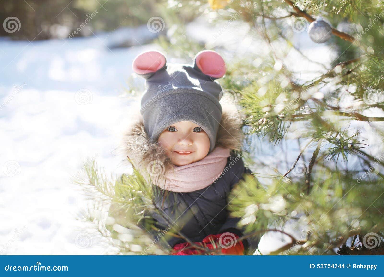 滑稽的孩子画象在圣诞树附近的在冬天