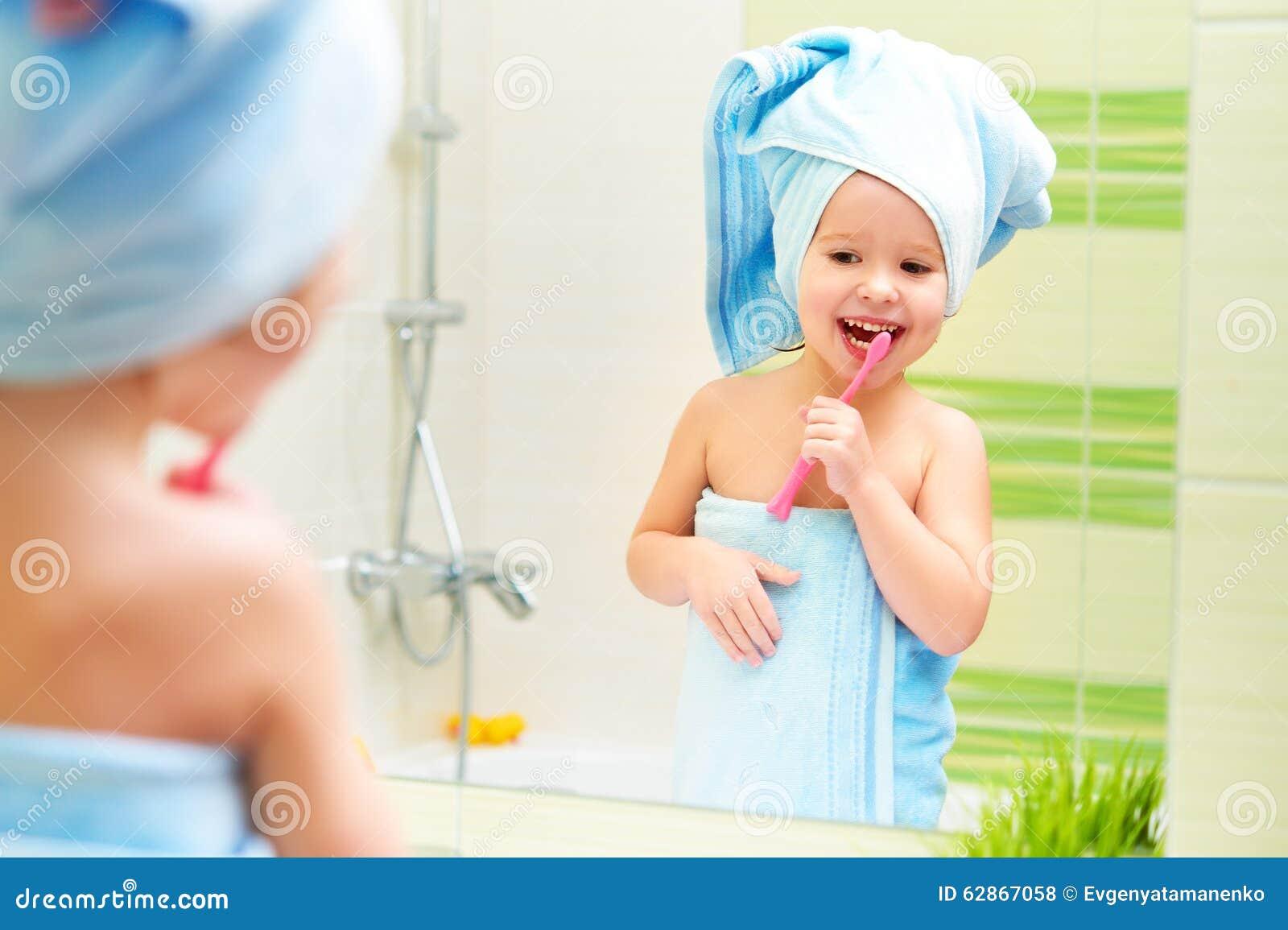 滑稽的小女孩清洗牙与牙刷在卫生间里