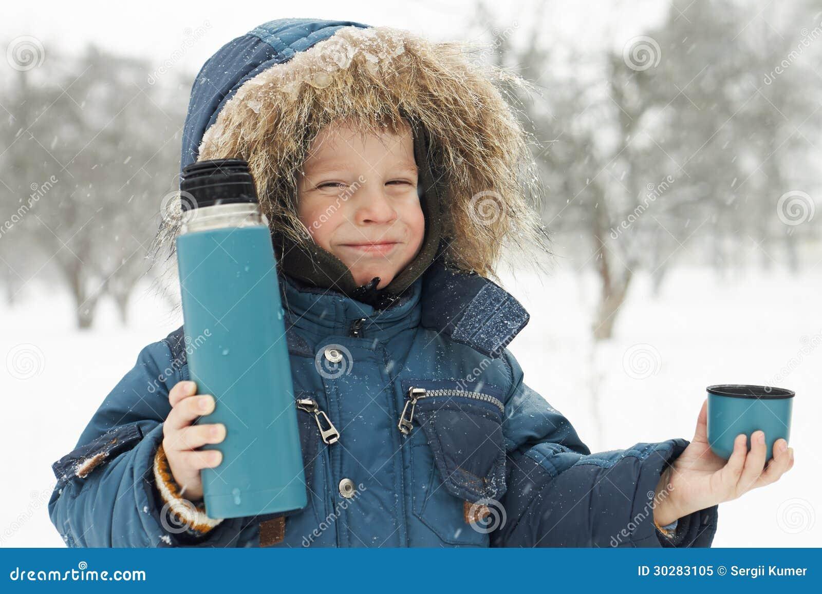 滑稽的小男孩邀请喝从热水瓶的热的茶
