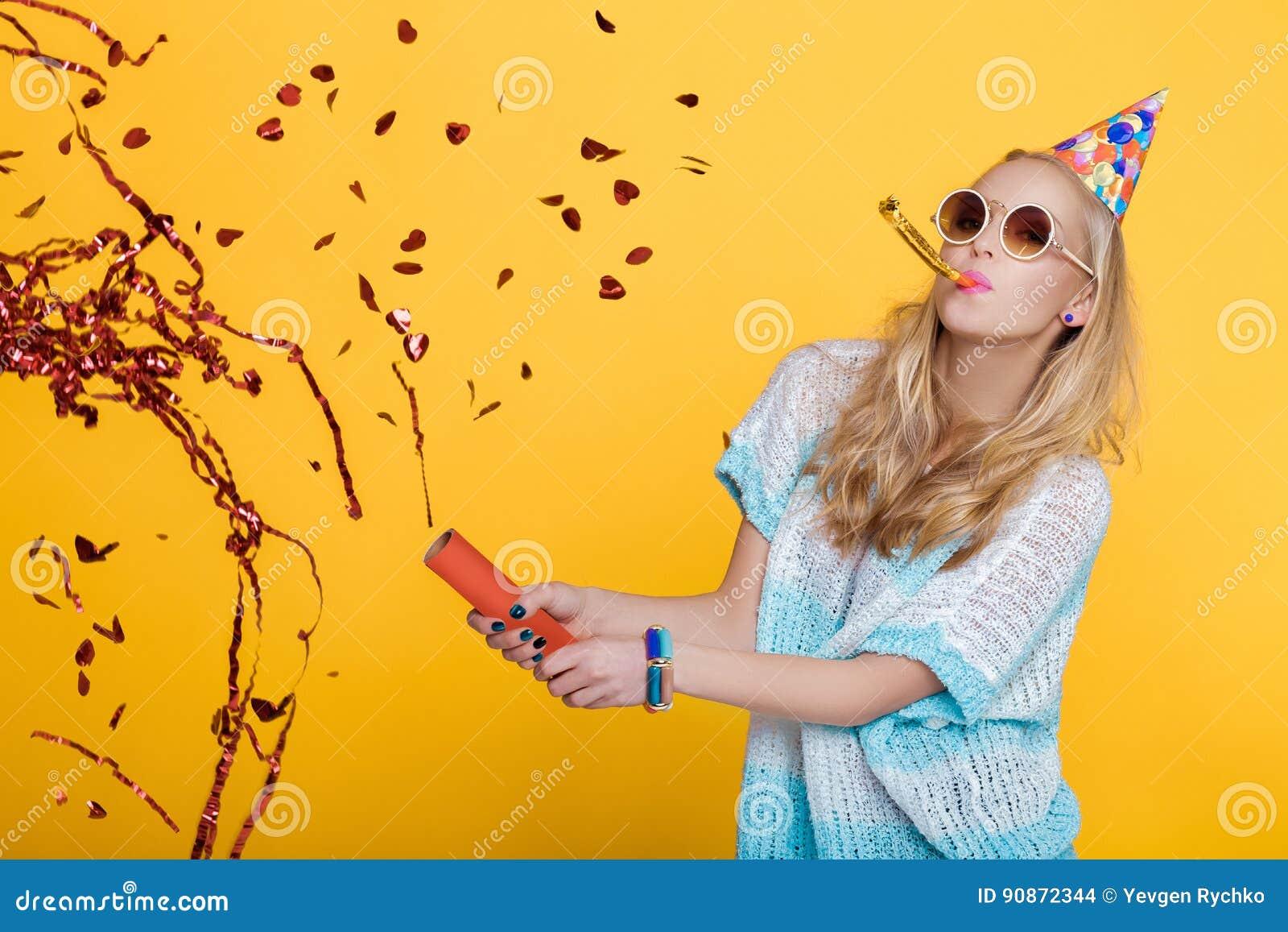滑稽的白肤金发的妇女和在黄色背景的红色五彩纸屑画象生日帽子的 庆祝和党