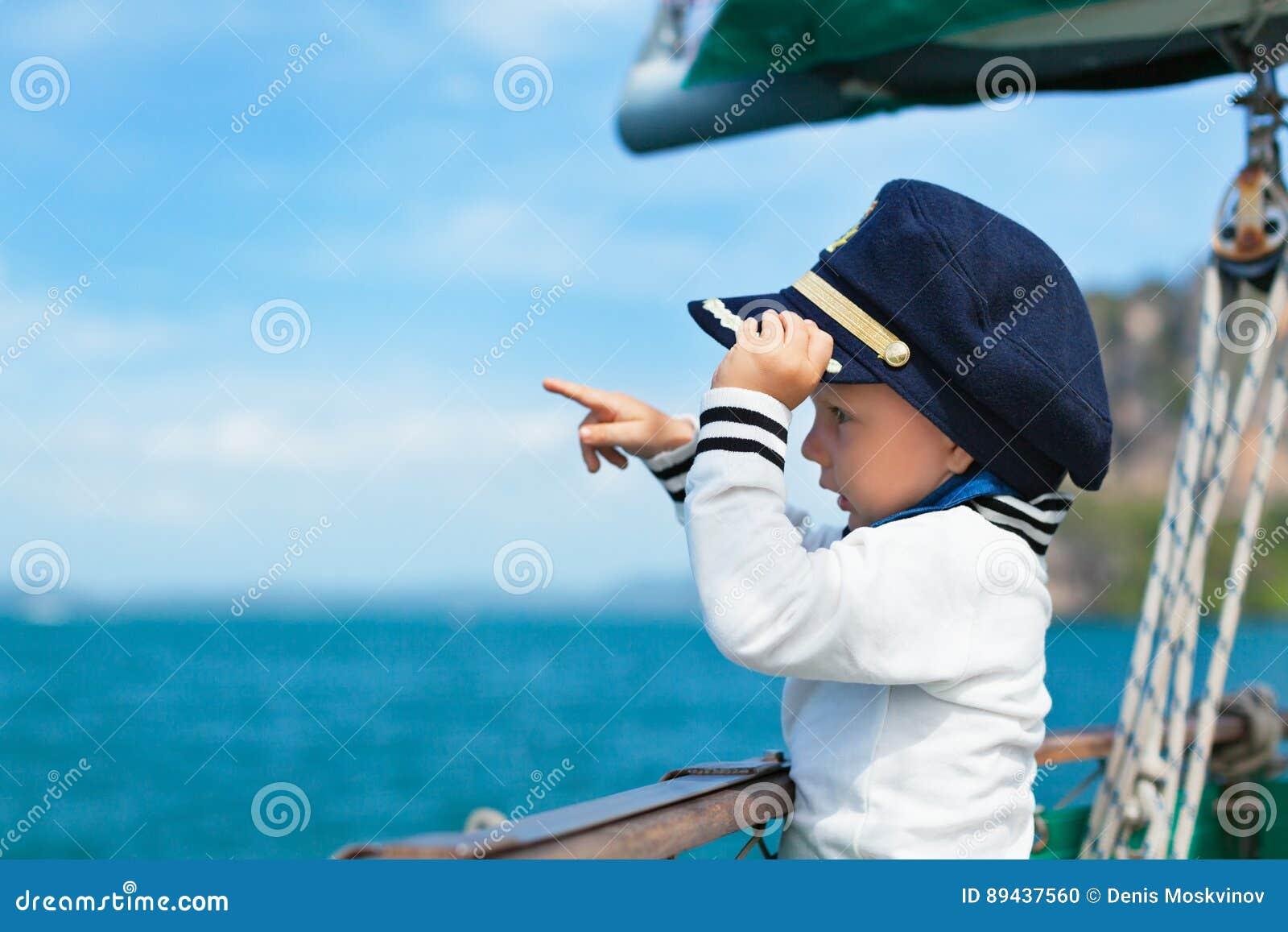 滑稽的矮小的小上尉在船上航行游艇