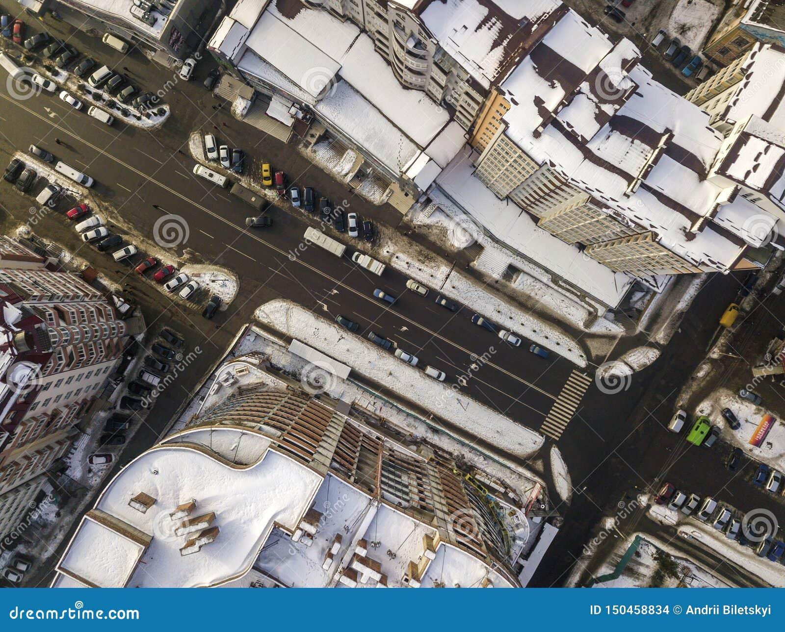 空中黑白现代城市冬天顶视图有高楼,停放的和移动的汽车的沿有路标的街道
