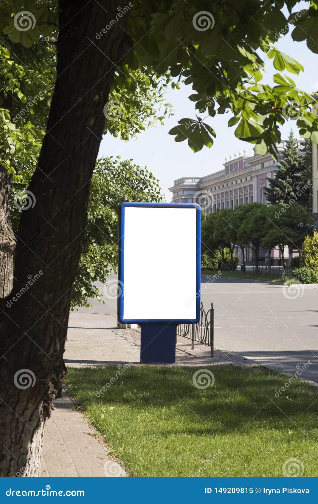 空白嘲笑在城市背景的垂直的街道海报广告牌