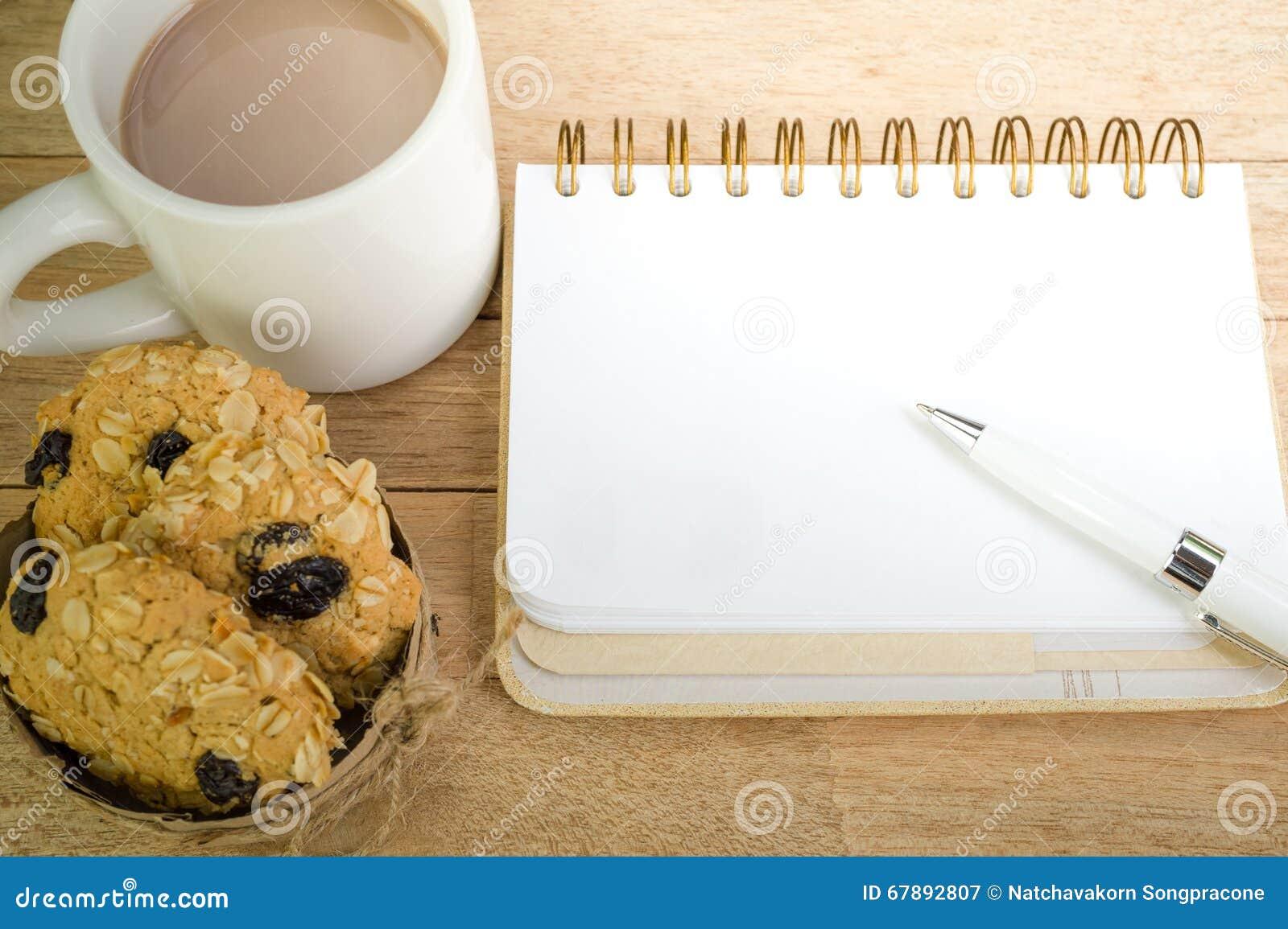 空白的笔记本用在木背景的咖啡和燕麦曲奇饼