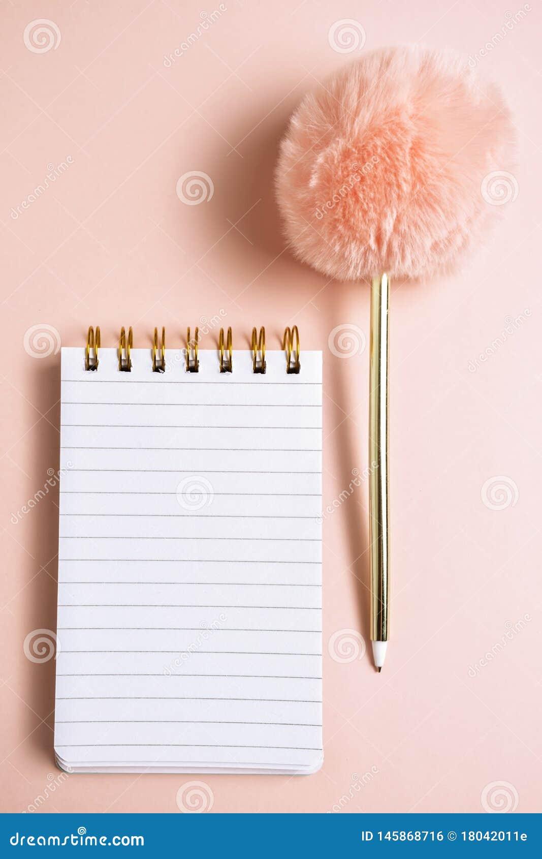 空白的笔记本顶视图有滑稽的蓬松笔的在与拷贝空间,垂直的构成的桃红色淡色背景
