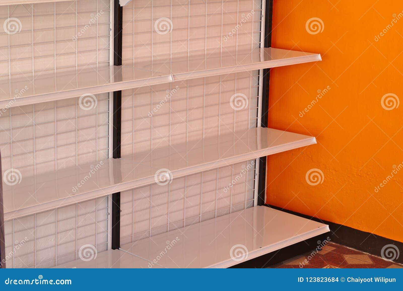 空的架子在有橙色墙壁的超级市场