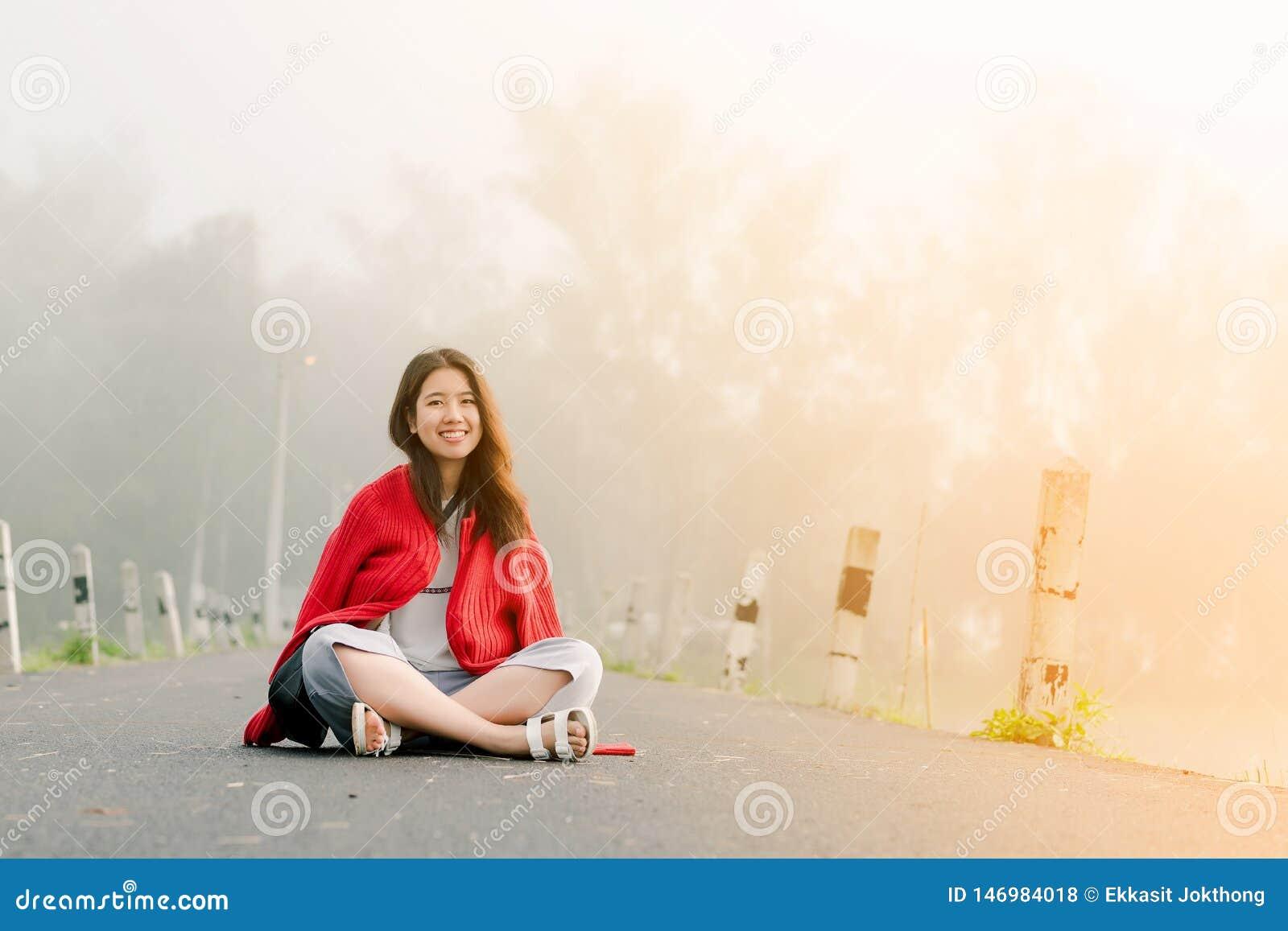 穿一件红色毛线衣的亚裔少年坐在路中间由在早晨薄雾和早晨阳光的水库