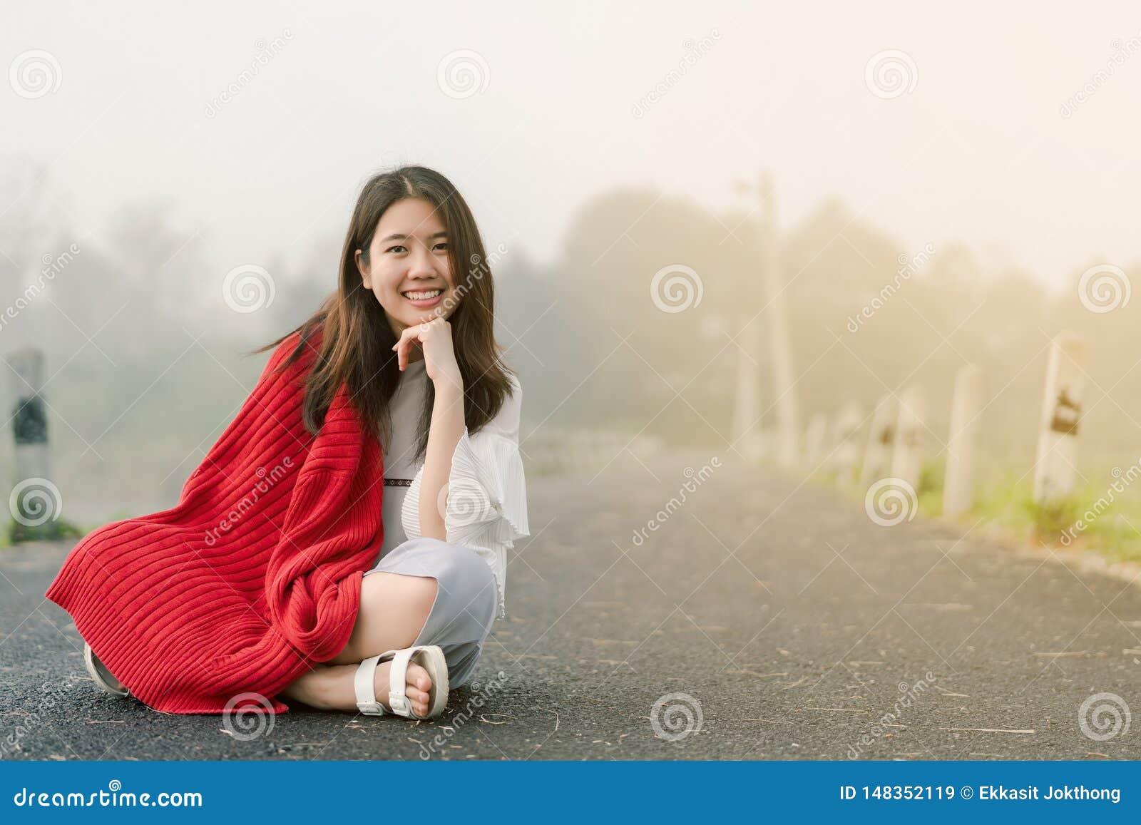 穿一件红色毛线衣的亚裔少年坐在路中间由在早晨薄雾的水库