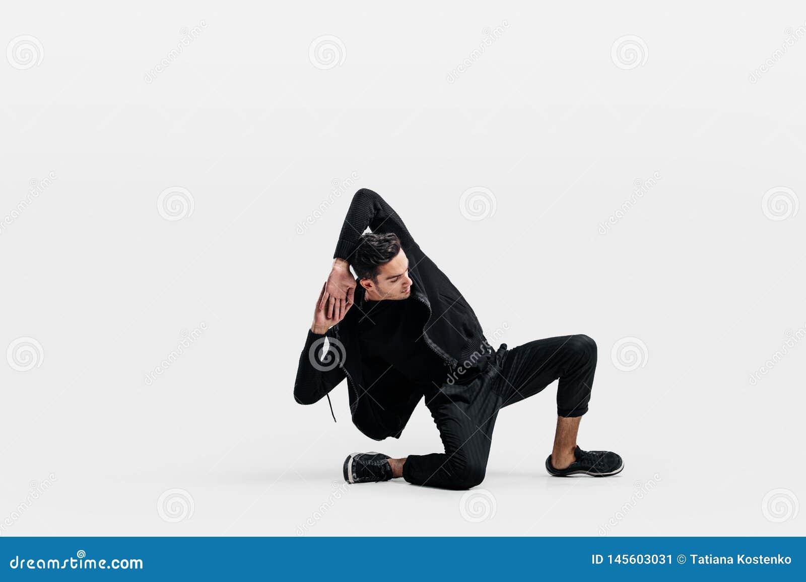 穿一件黑运动衫和黑色裤子的英俊的年轻人跳舞做在地板上的breakdance跳舞的运动