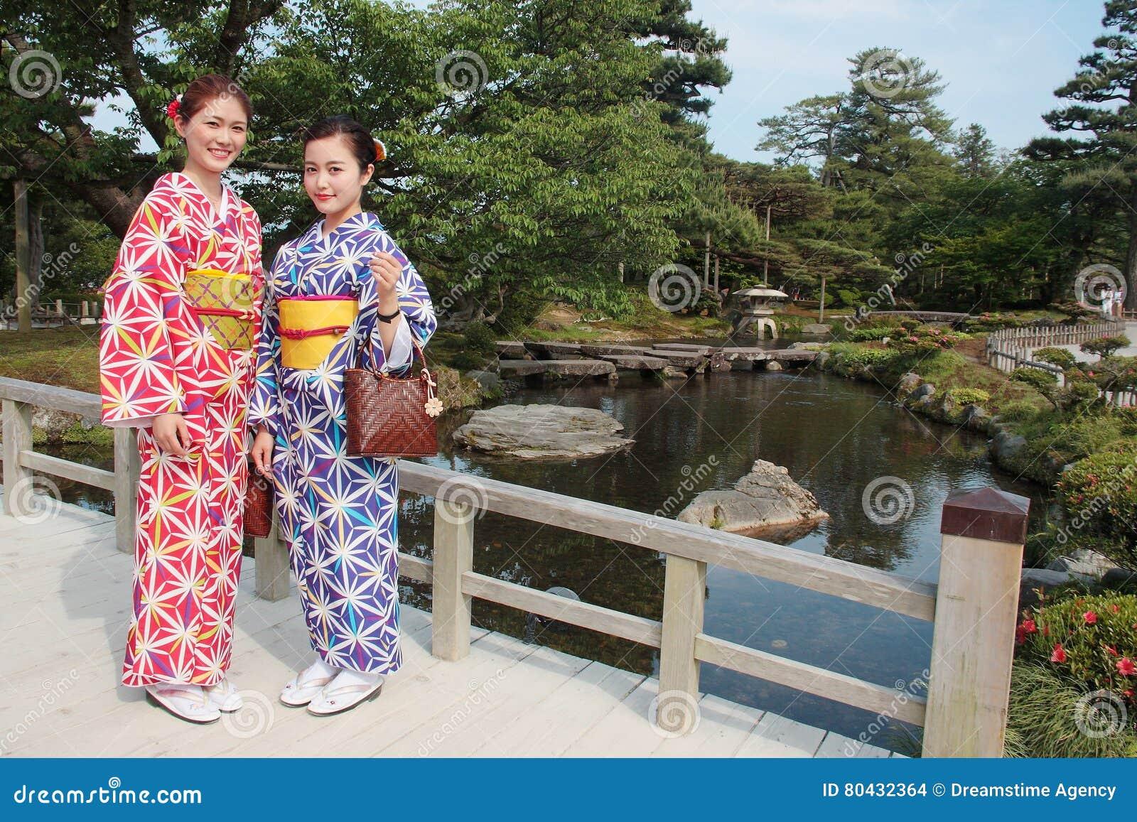 穿五颜六色的传统日本和服在Kenrokuen,著名日本风景庭院的女孩夫妇在今池日本